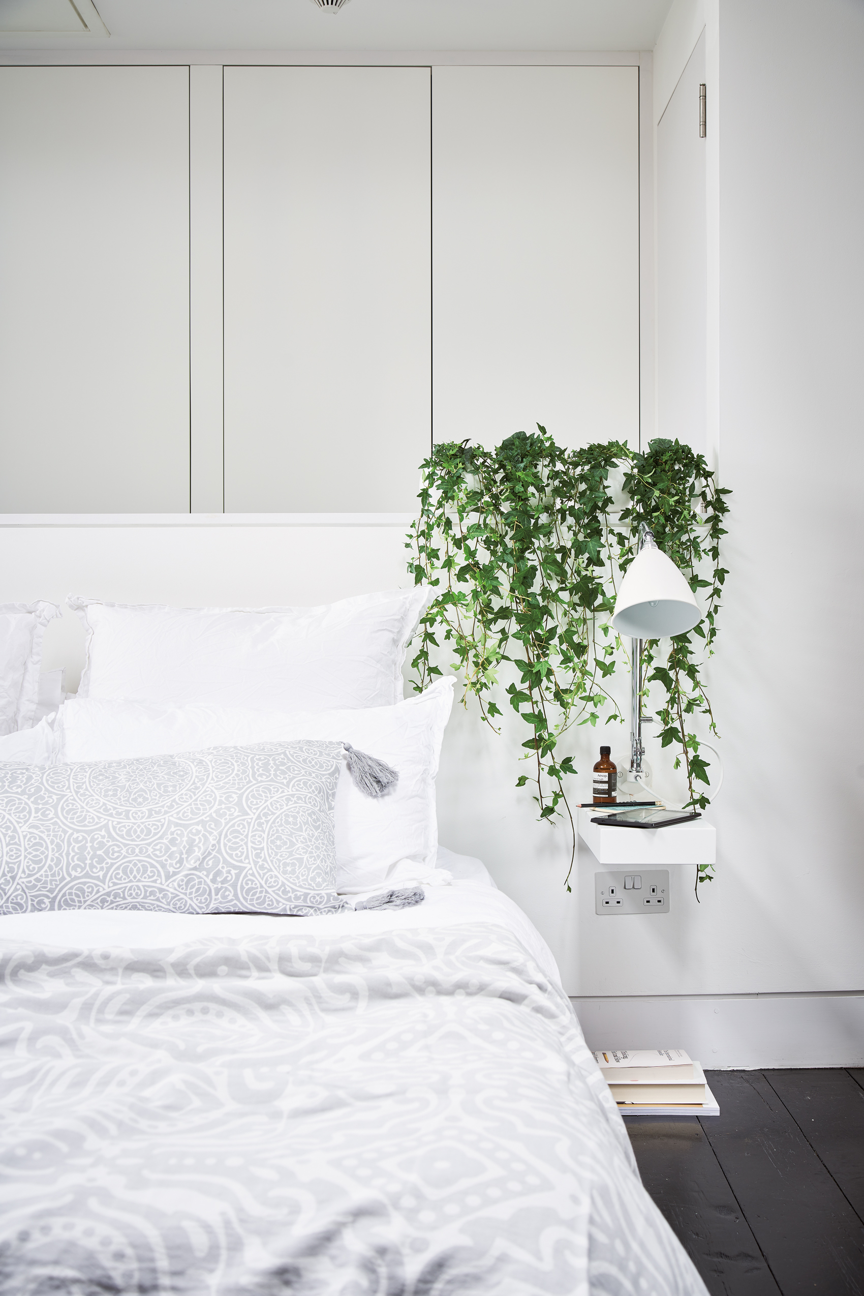 A line up of tiny, trailing Hedera helix (English ivy) hanging down from pots grouped on the bed head, turns a plain bedside shelf into a striking design statement. Room featured At Home With Plants (Nick Pope/Mitchell Beazley/PA)