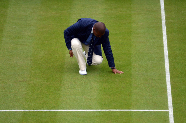 The umpire checks the moisture on the grass during the match between Dan Evans and Alexandr Dolgopolov on day Three of the Wimbledon Championships at the All England Lawn Tennis and Croquet Club, Wimbledon.
