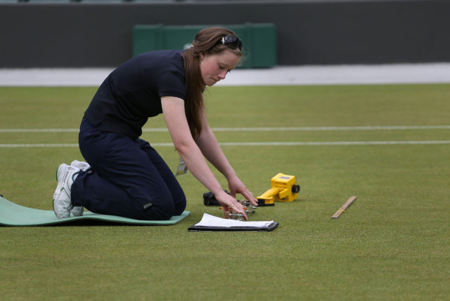 Laura Budimir, a research officer for the Sports Turf Research Institute checks live grass cover on Court 1 on day six of the Wimbledon Championships at the All England Lawn Tennis and Croquet Club, Wimbledon.