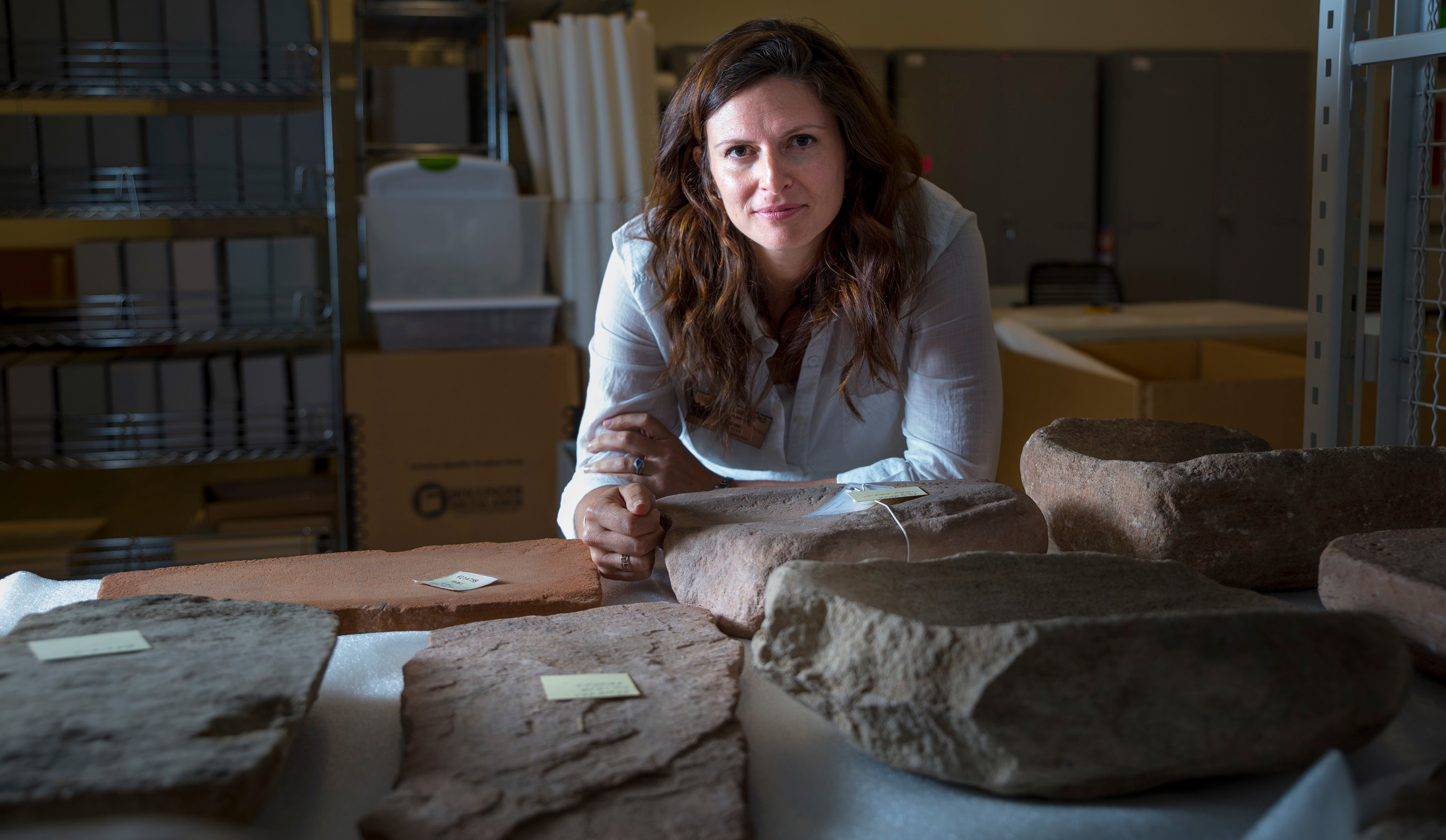 Lisbeth Louderback, assistant professor of anthropology and curator of archaeology at the Natural History Museum of Utah, stands behind large stone metates, the grindstones on which ancient Native Americans processed their food.