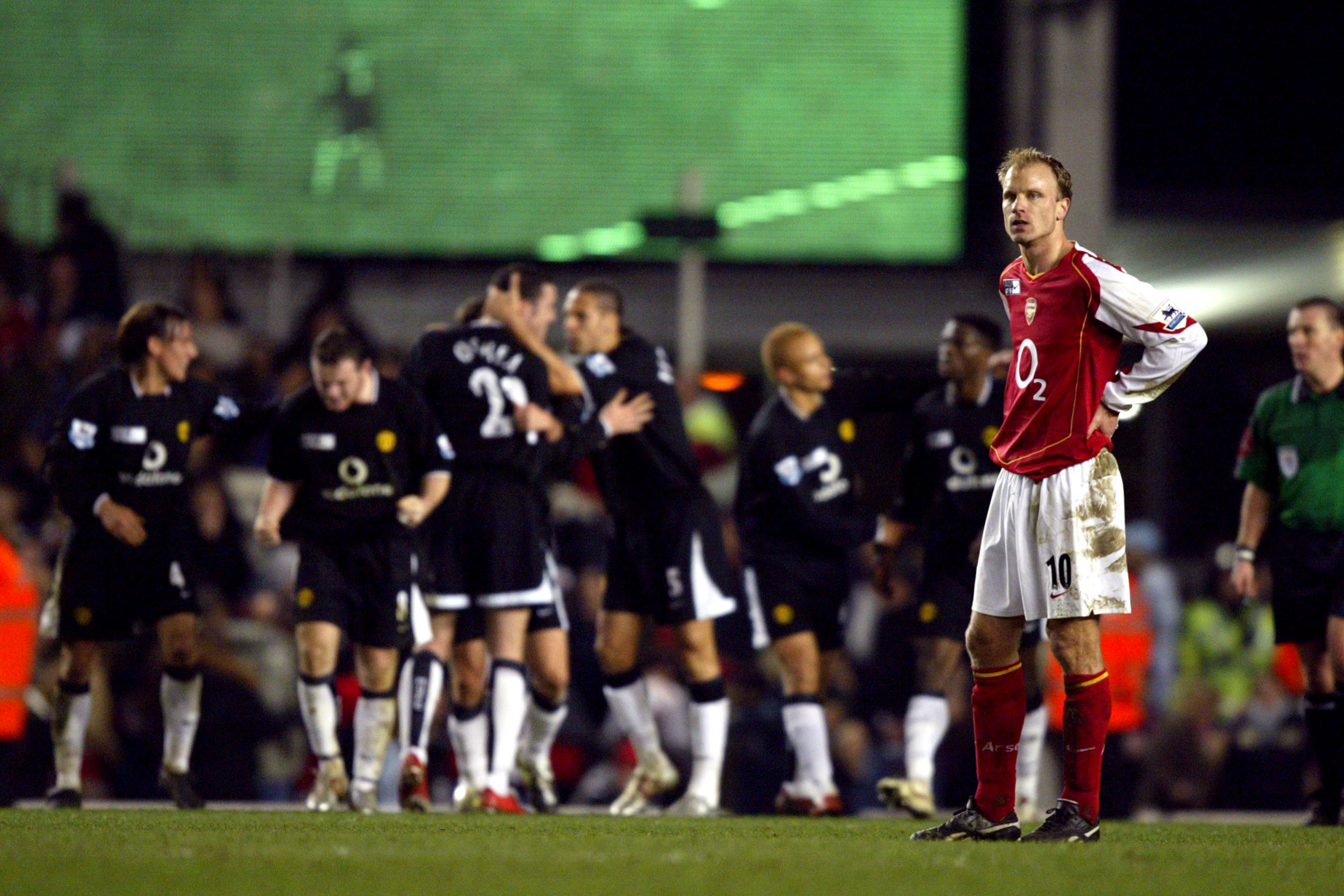 Manchester United players celebrate while Dennis Bergkamp looks on