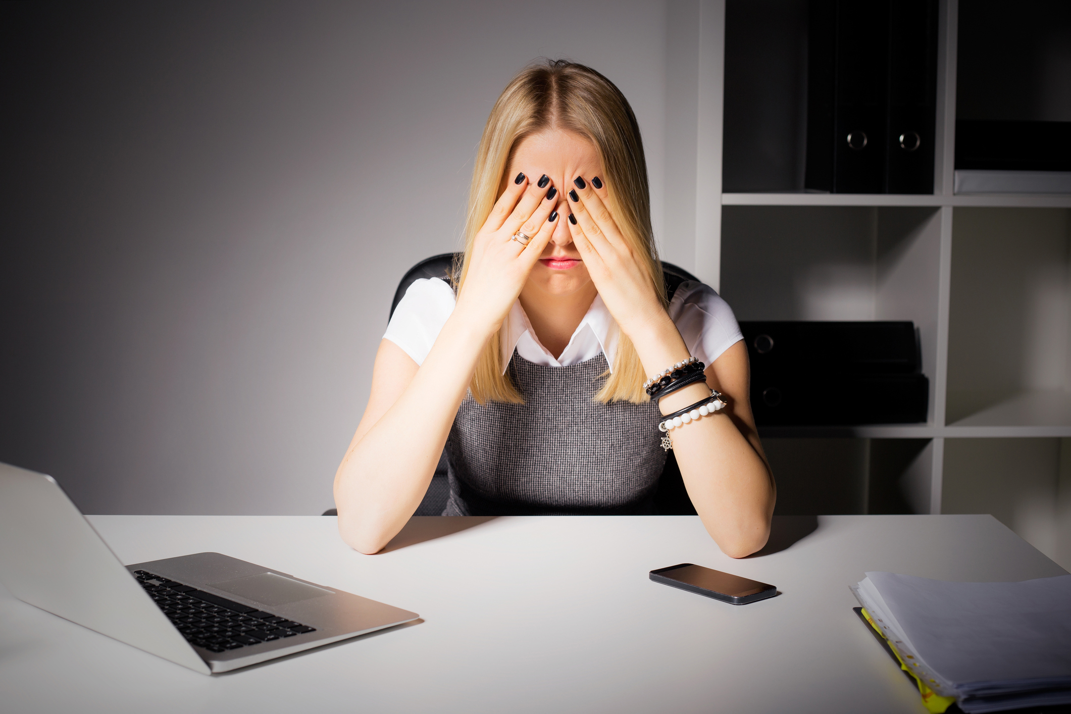 Woman sitting in her office with her eyes covered (ThinkStock/PA)