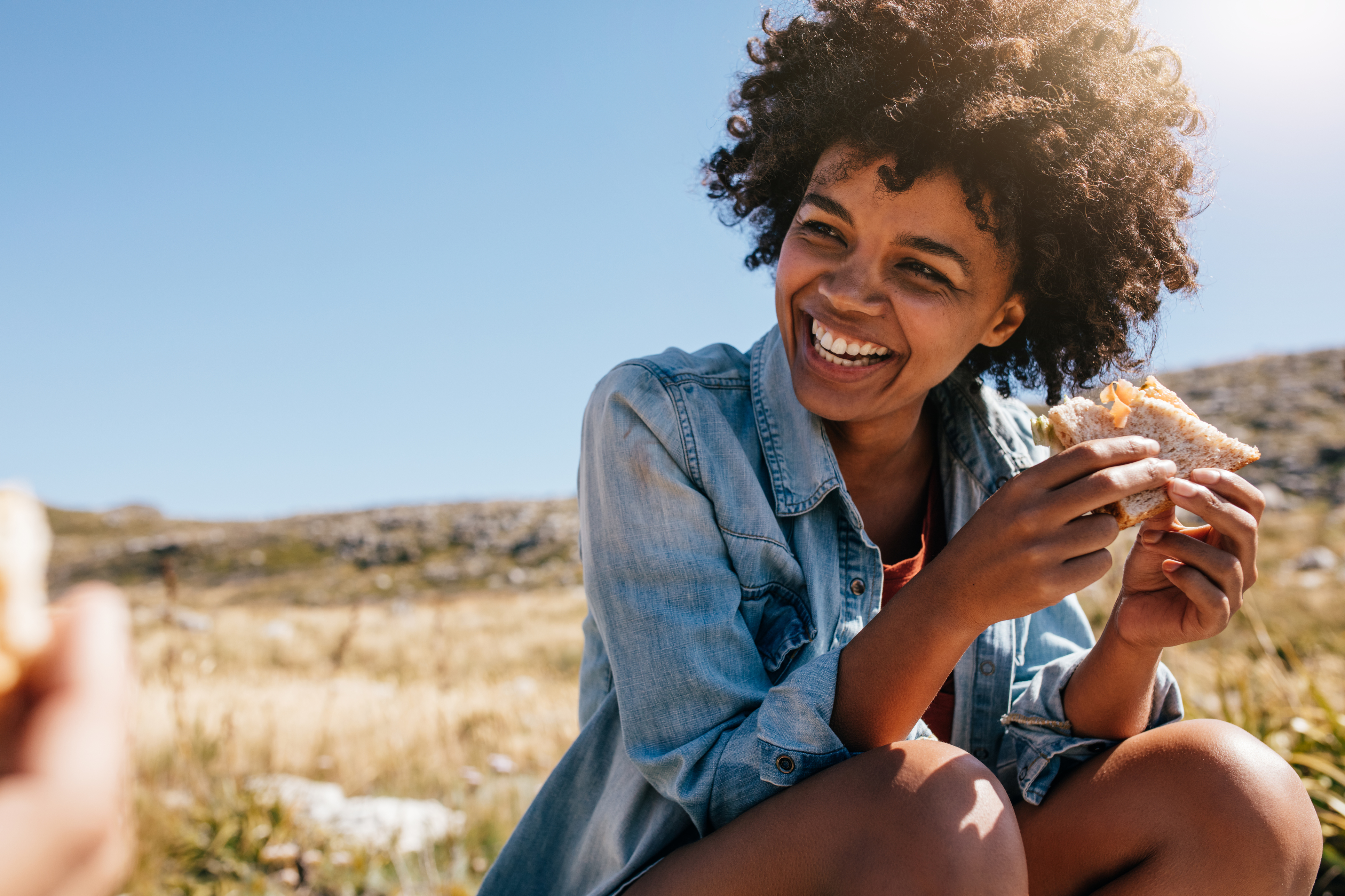 Generic photo of young woman looking happy eating a sandwich outdoors (Thinkstock/PA)