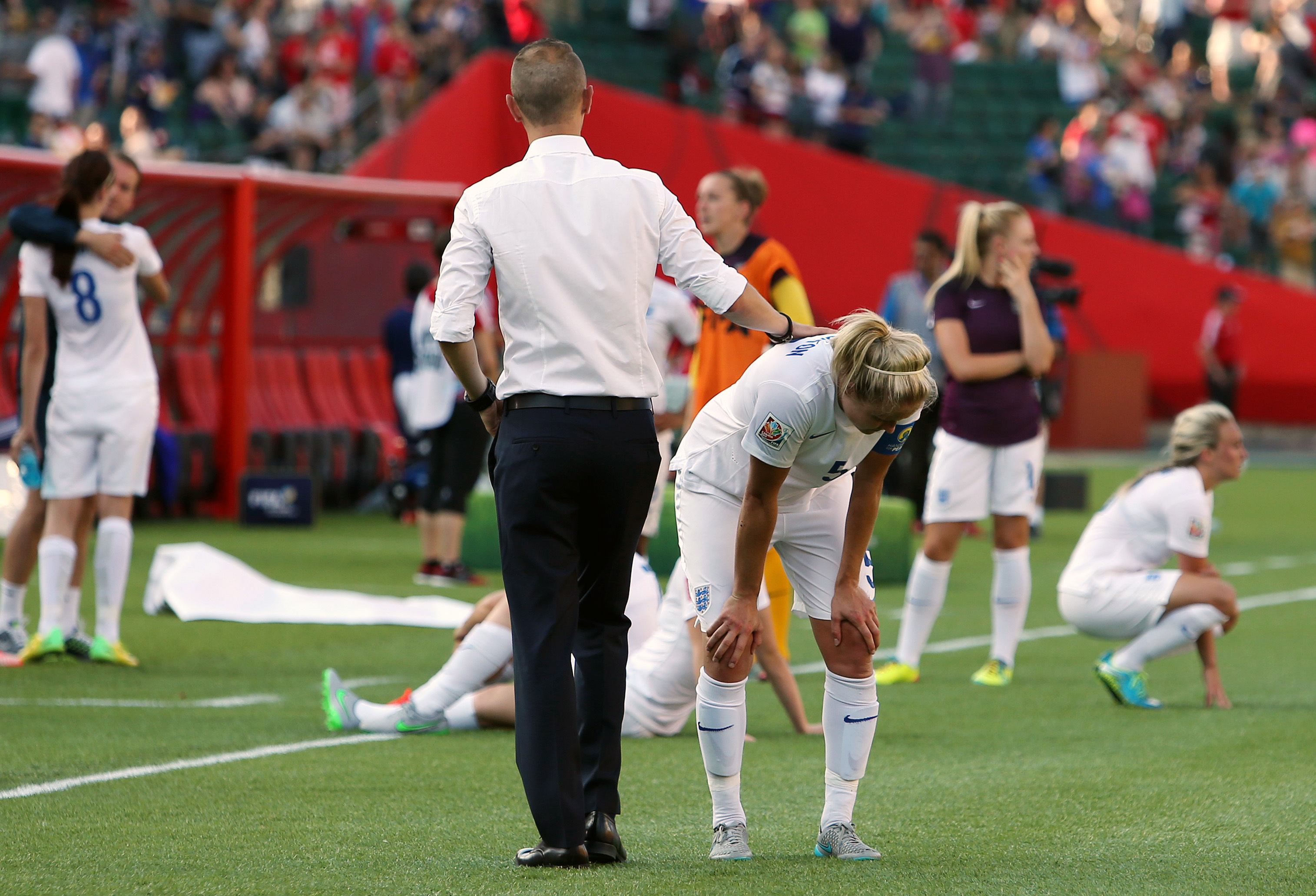 England's head coach Mark Sampson consoles his players after defeat at the 2015 World Cup against Japan