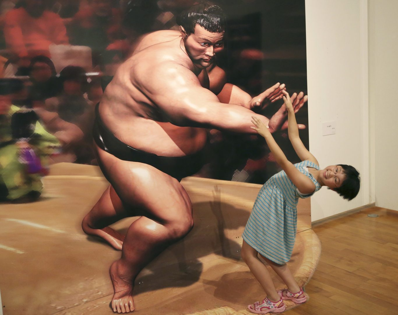 A girl poses with a 3D image at a 3D trick art exhibition by Japanese artist Masashi Hattori in Kawasaki, near Tokyo, Saturday, Aug. 5, 2017. (Koji Sasahara/AP/PA)