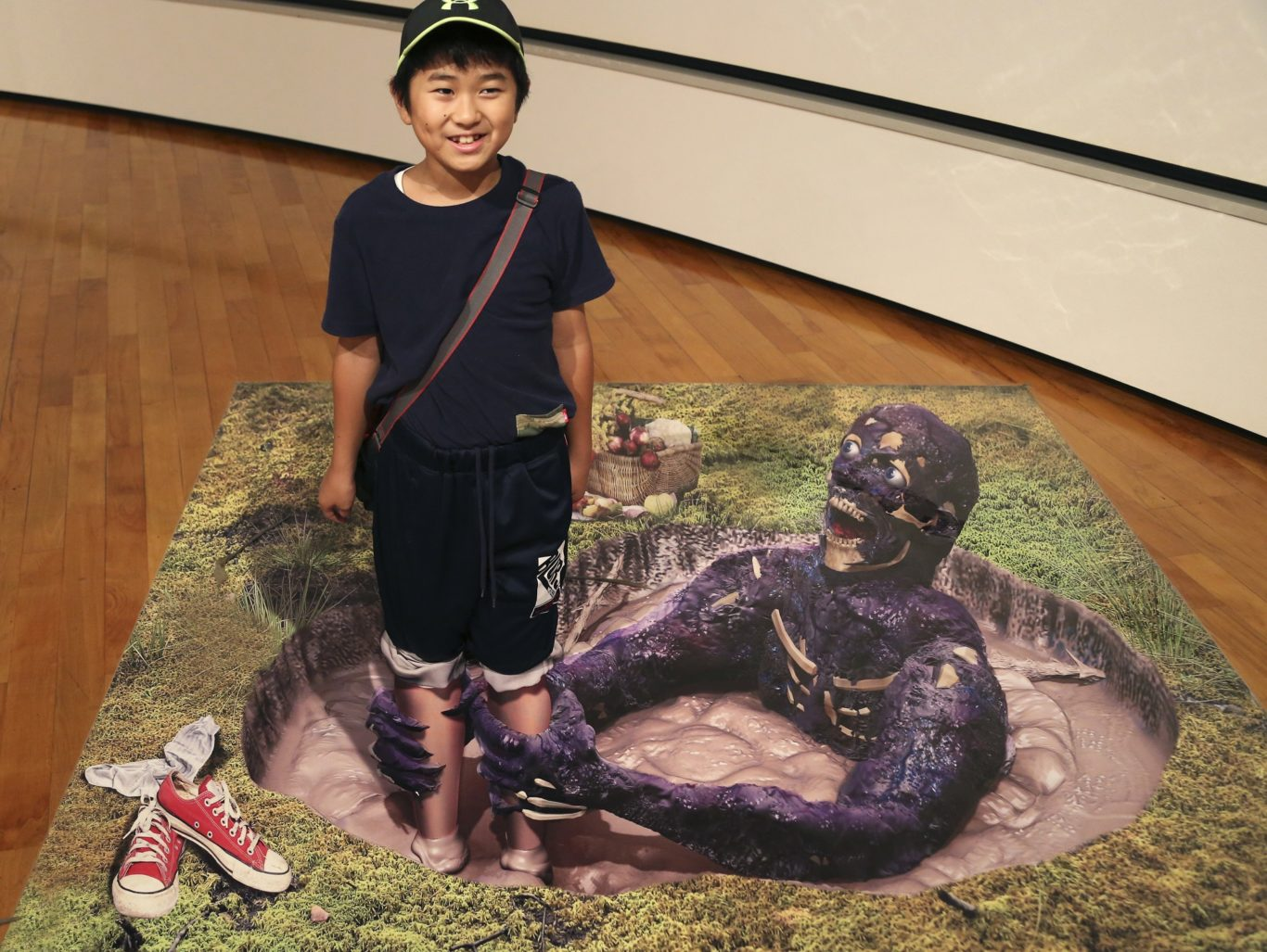 A boy poses with a 3D image at a 3D trick art exhibition by Japanese artist Masashi Hattori in Kawasaki, near Tokyo, Saturday, Aug. 5, 2017. (Koji Sasahara/AP/PA