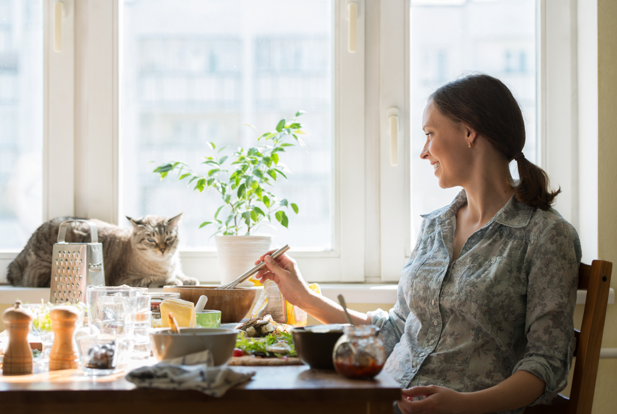 A woman prepares food while a cat sits by the window in front of her (Thinkstock/PA)