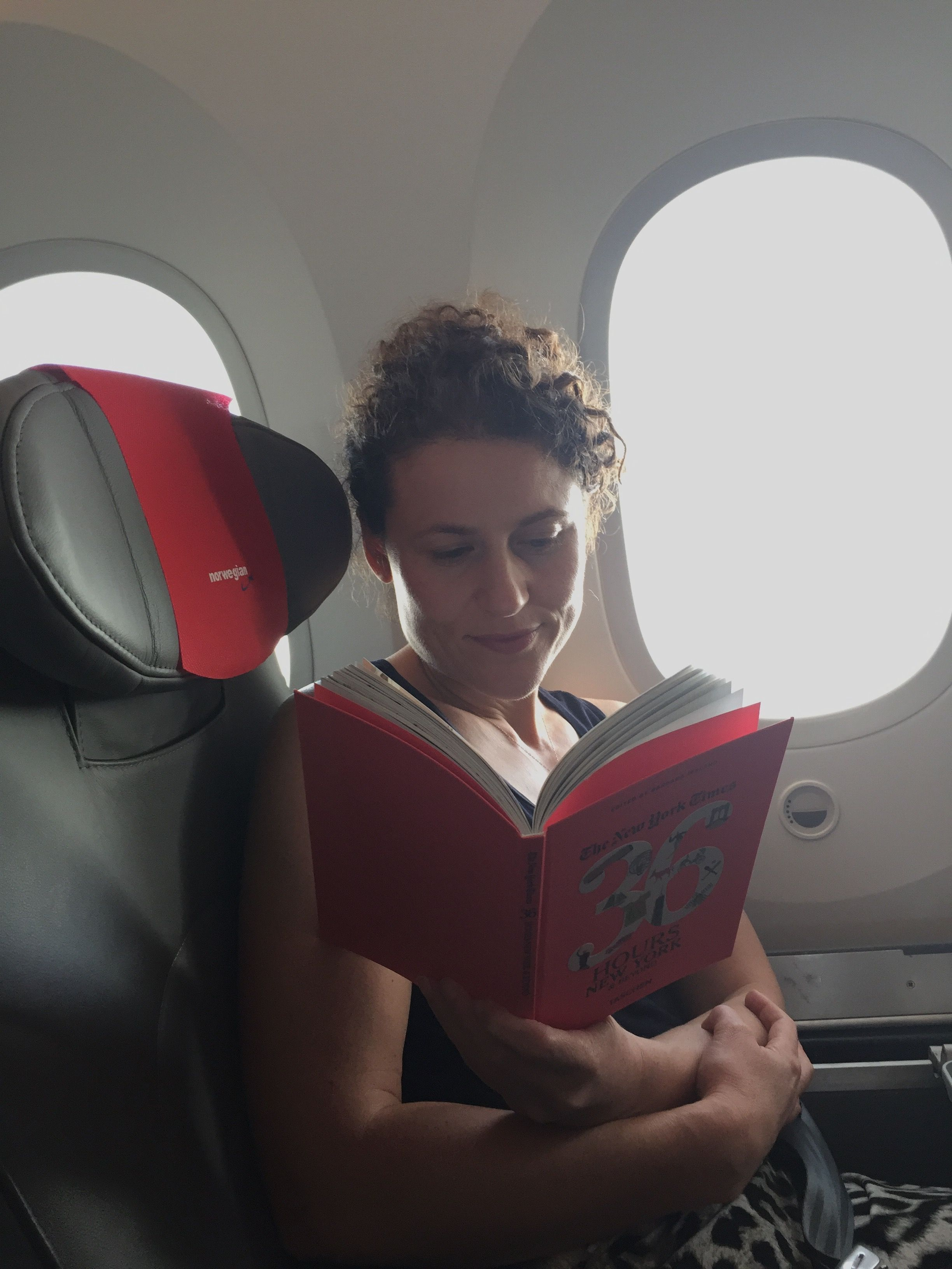 Sarah Marshall reading on flight to New York (Sarah Marshall/PA)
