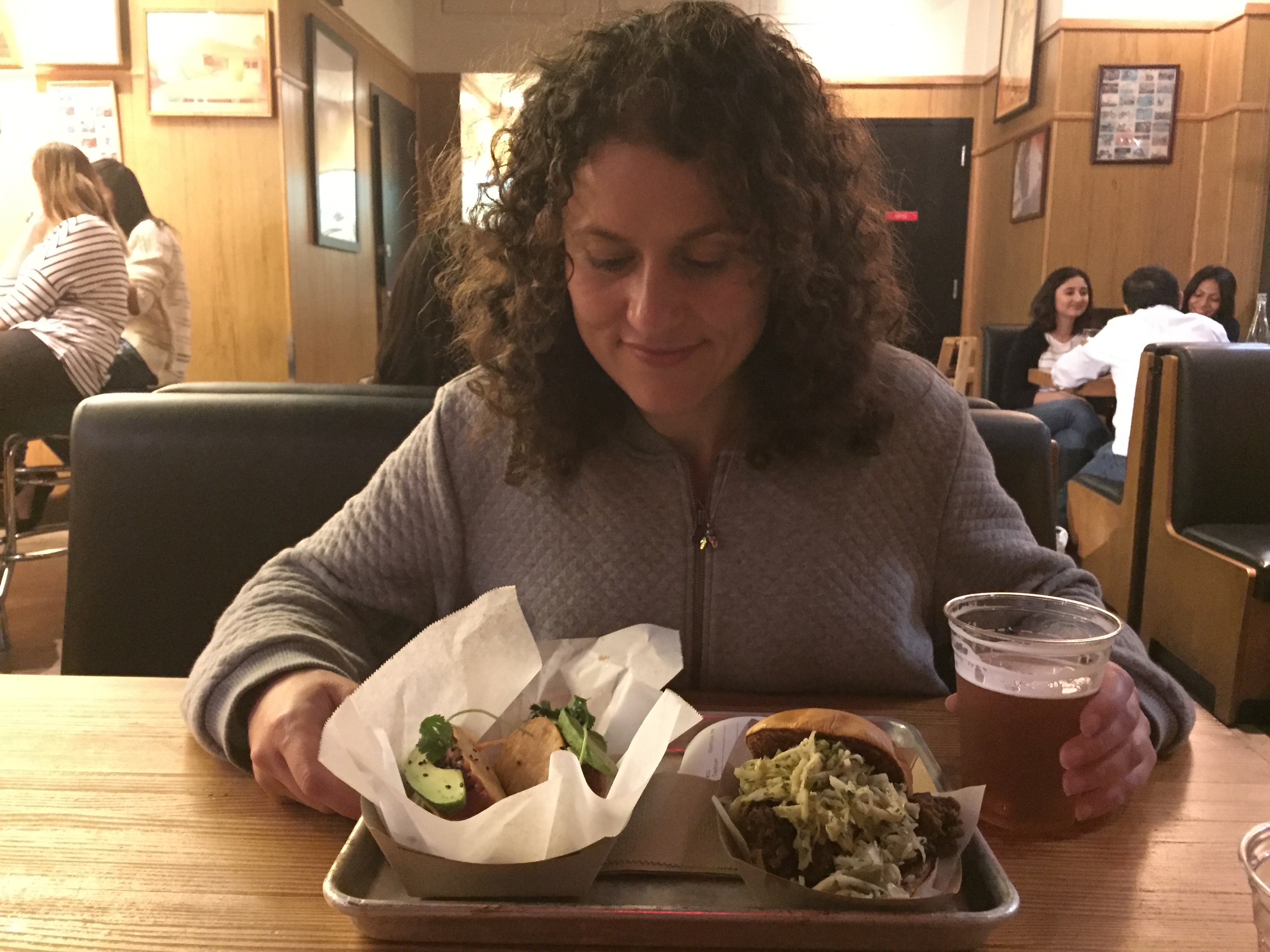 Girl eating a taco and beer