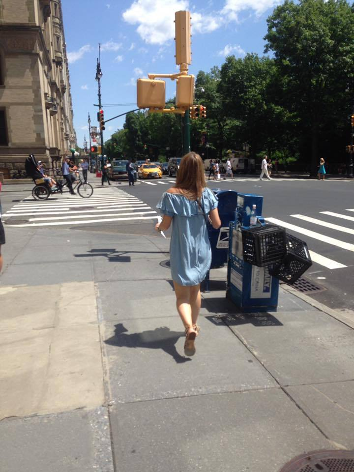 woman wearing a blue off the shoulder dress walking down a street in New York (Lulu Krausse/PA)