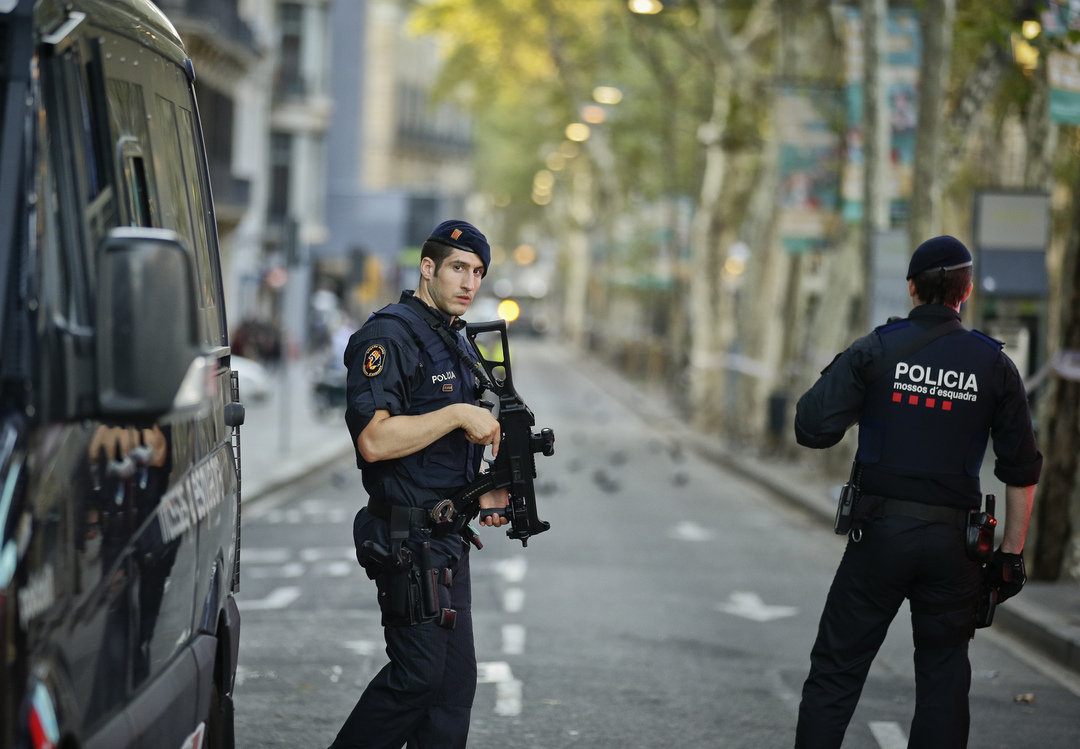 Armed police officers patrol a deserted street in Las Ramblas