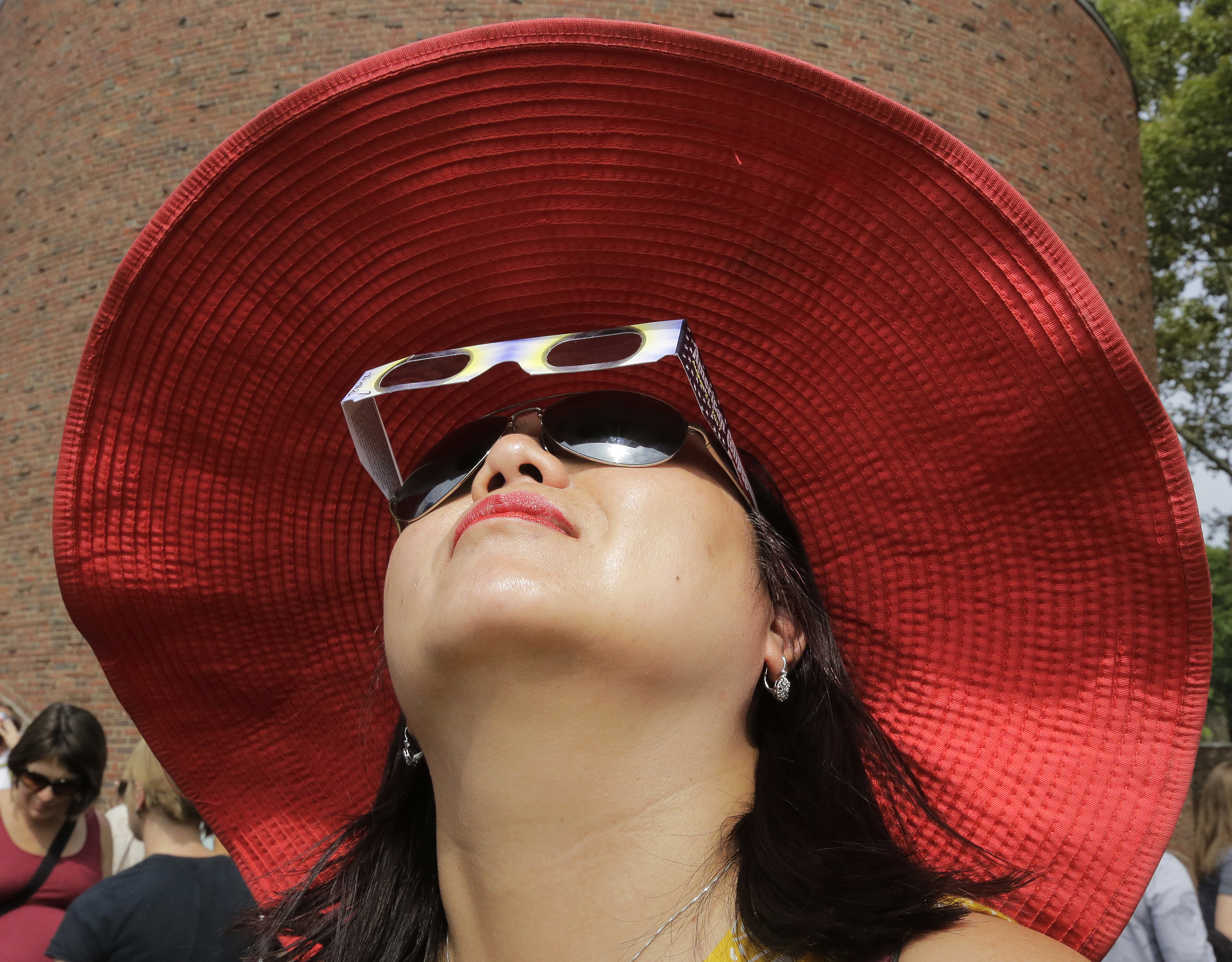 Someone uses protective glasses to view the solar eclipse