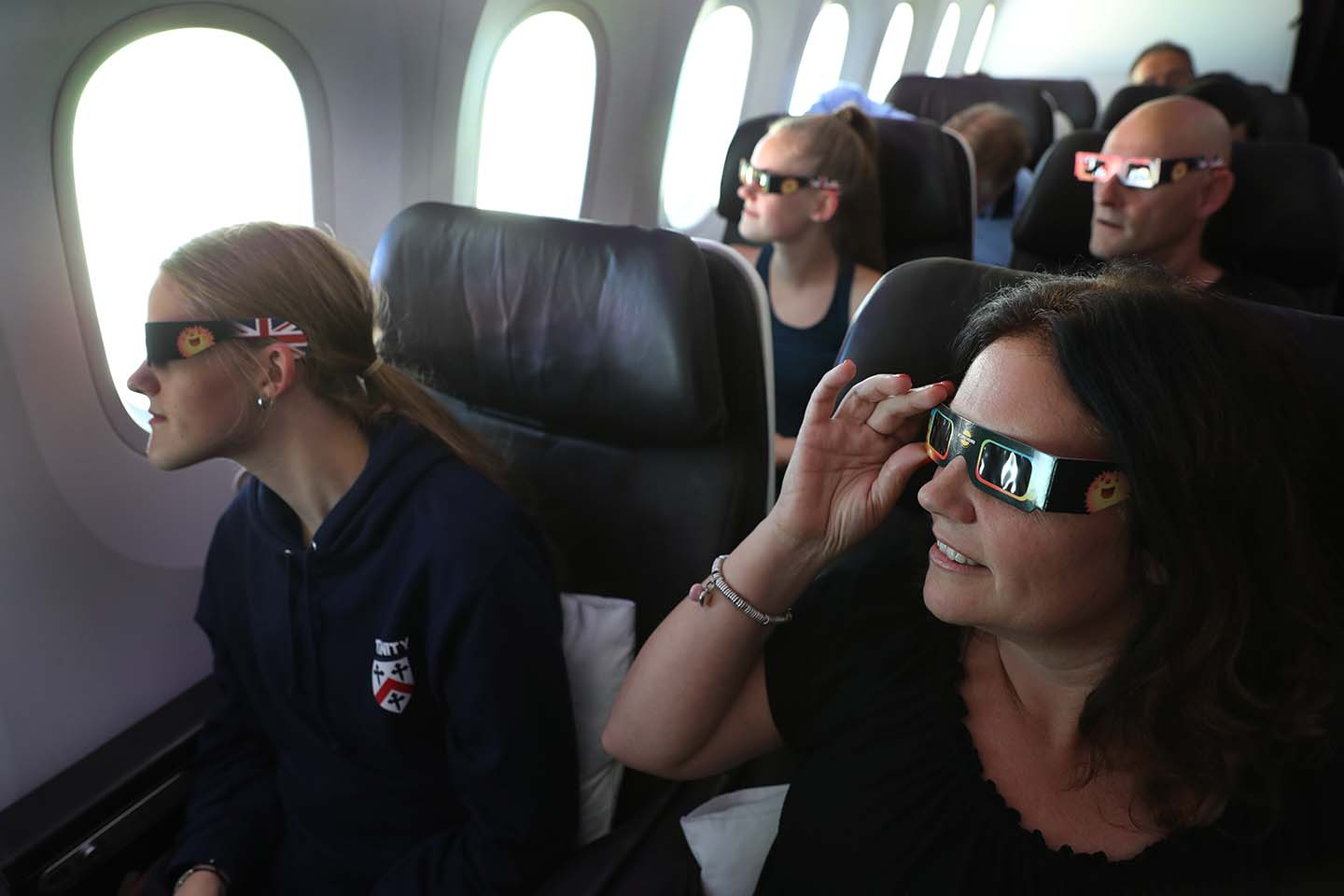 Passengers watch the start of the solar eclipse while flying over the United States