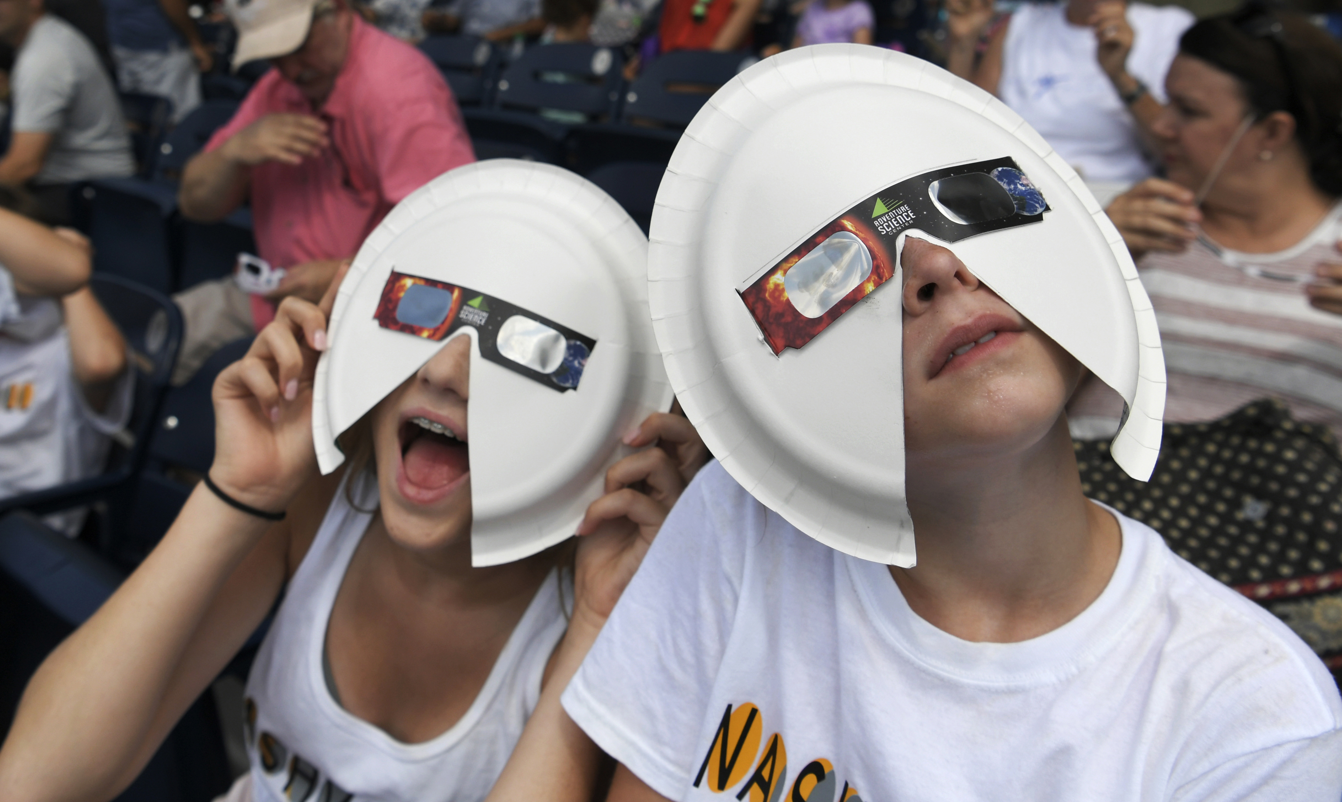 Two people wear makeshift eclipse glasses ahead of the solar eclipse
