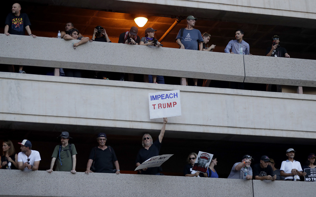People protest from a parking garage outside the Phoenix Convention Center