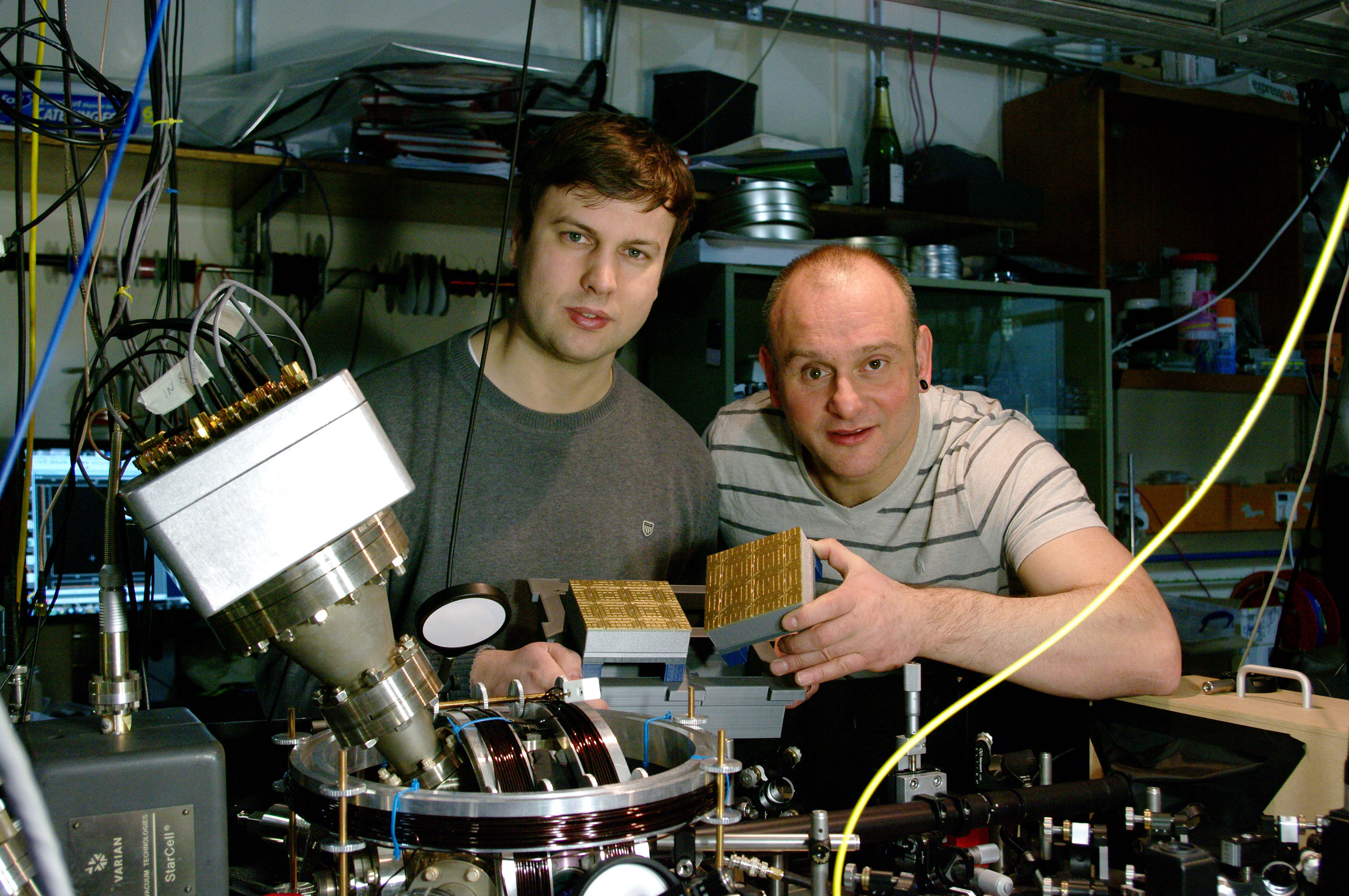 Professor Winfried Hensinger (right) and Dr Bjoern Lekitsch (left) with a quantum computer blueprint model behind a quantum computer prototype at the University of Sussex earlier in 2017