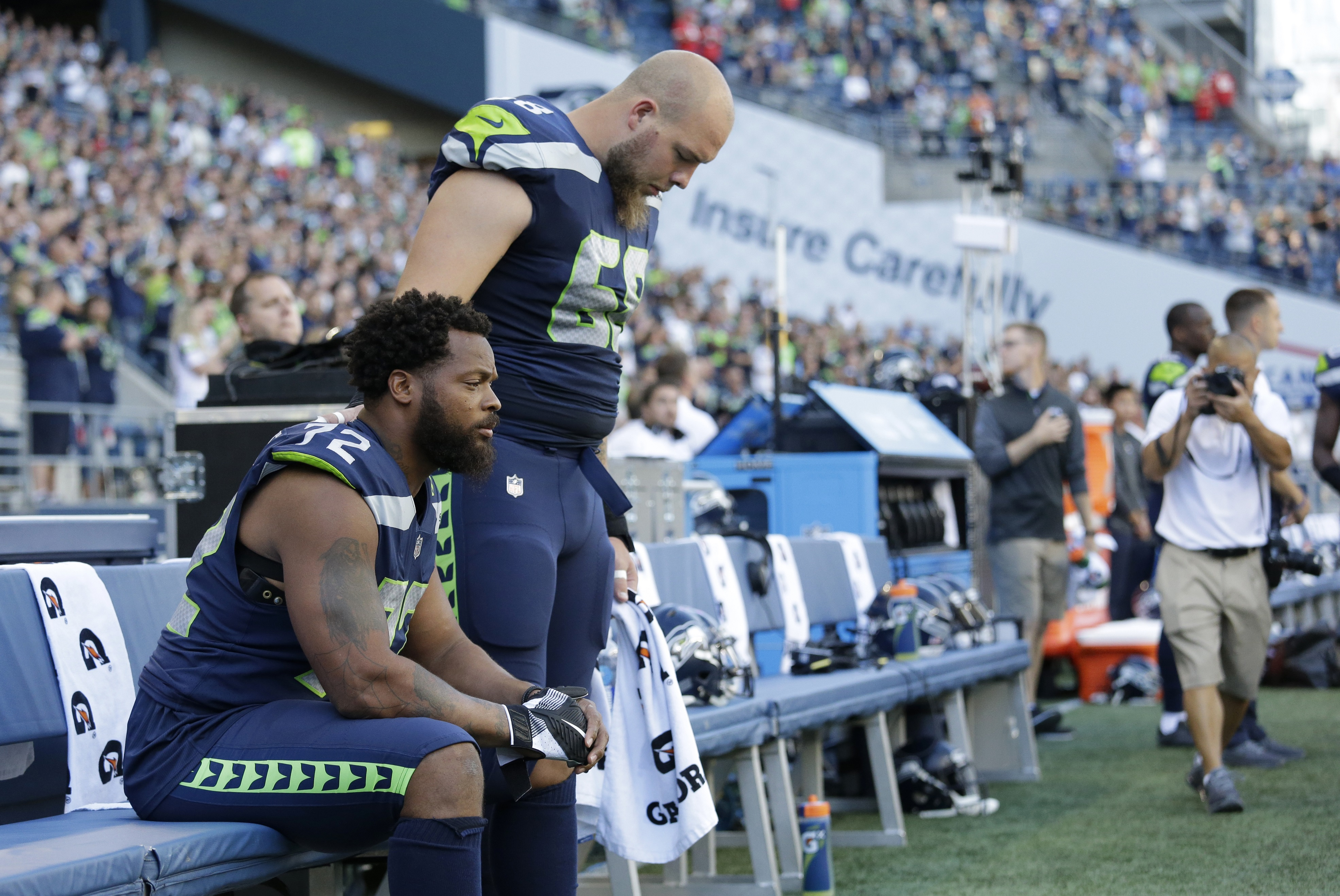 Seattle Seahawks defensive end Michael Bennett, left, sits during the singing of the national anthem as center Justin Britt, right, stands next to him