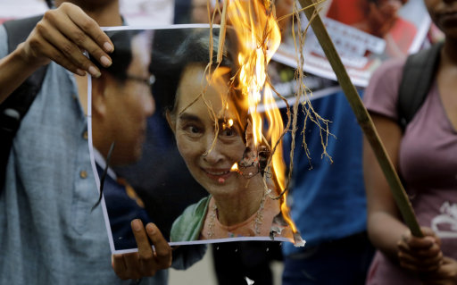 Protestor in India holds a burning image of Aung San Suu Kyi (Bikas Das/AP)