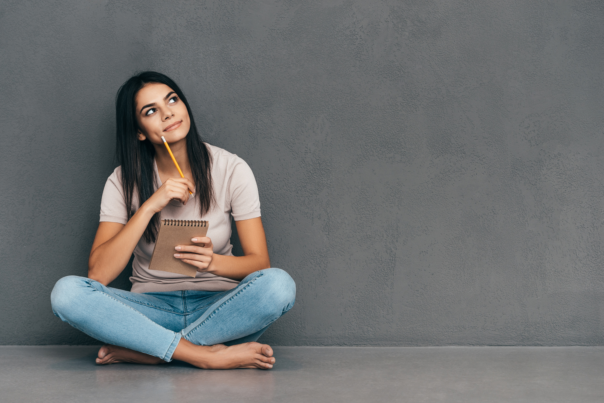 Attractive young woman in casual wear holding notebook and pen while sitting barefoot and against grey background (Thinkstock/PA)