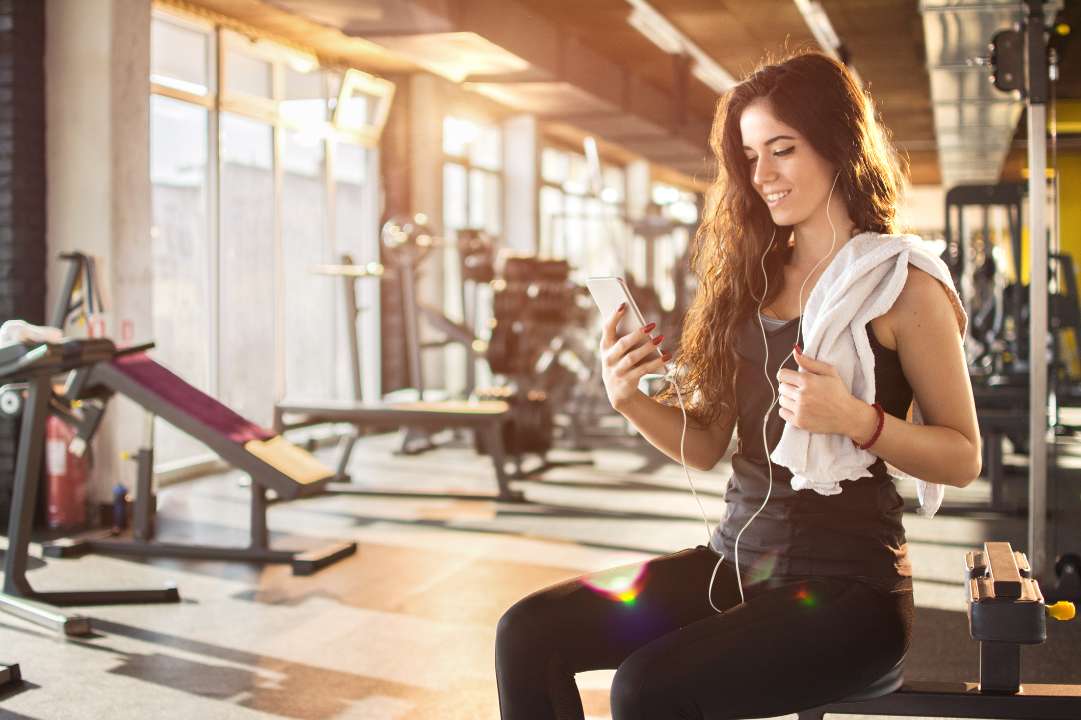 Generic photo of young woman in gym looking at her phone (Thinkstock/PA)