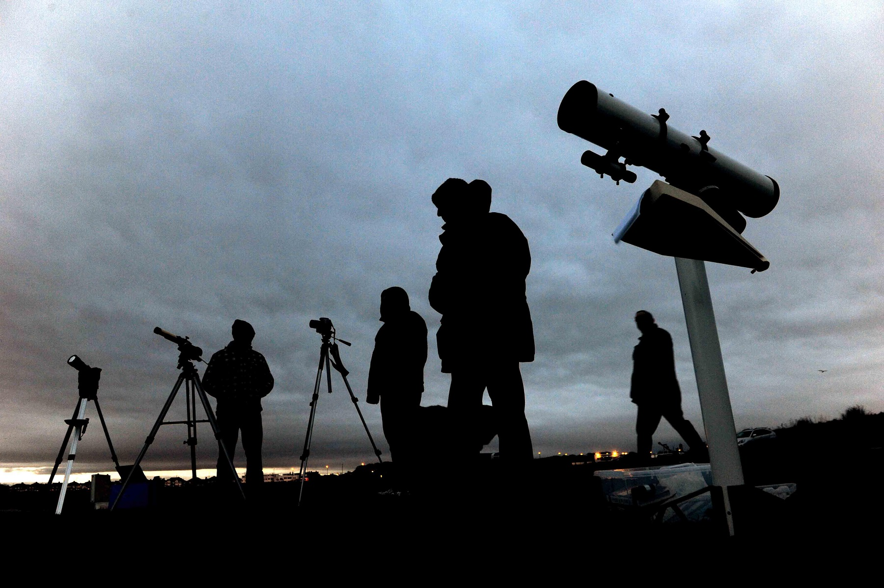 People stand with telescopes