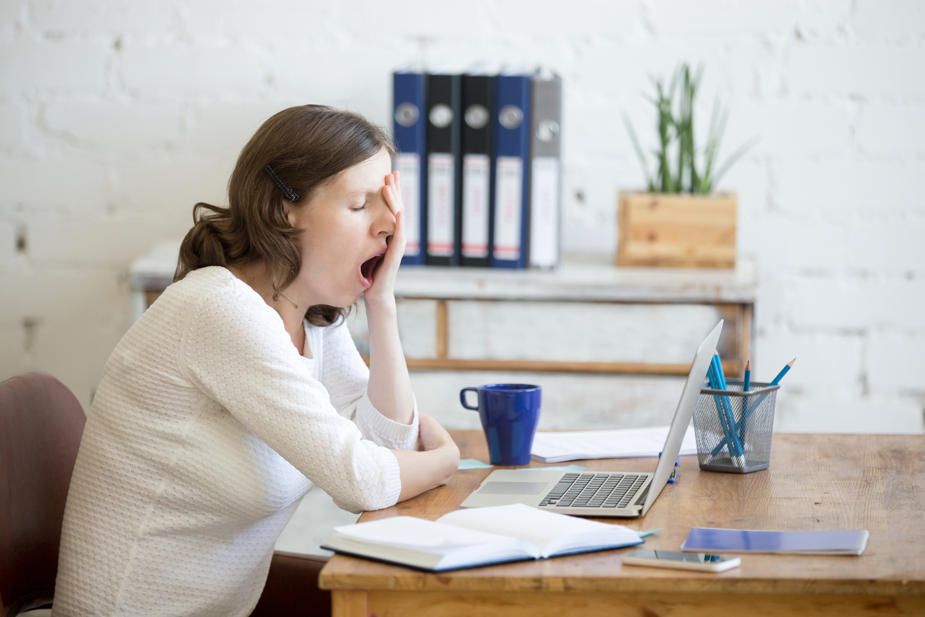 A woman yawning at her desk (Thinkstock/PA)