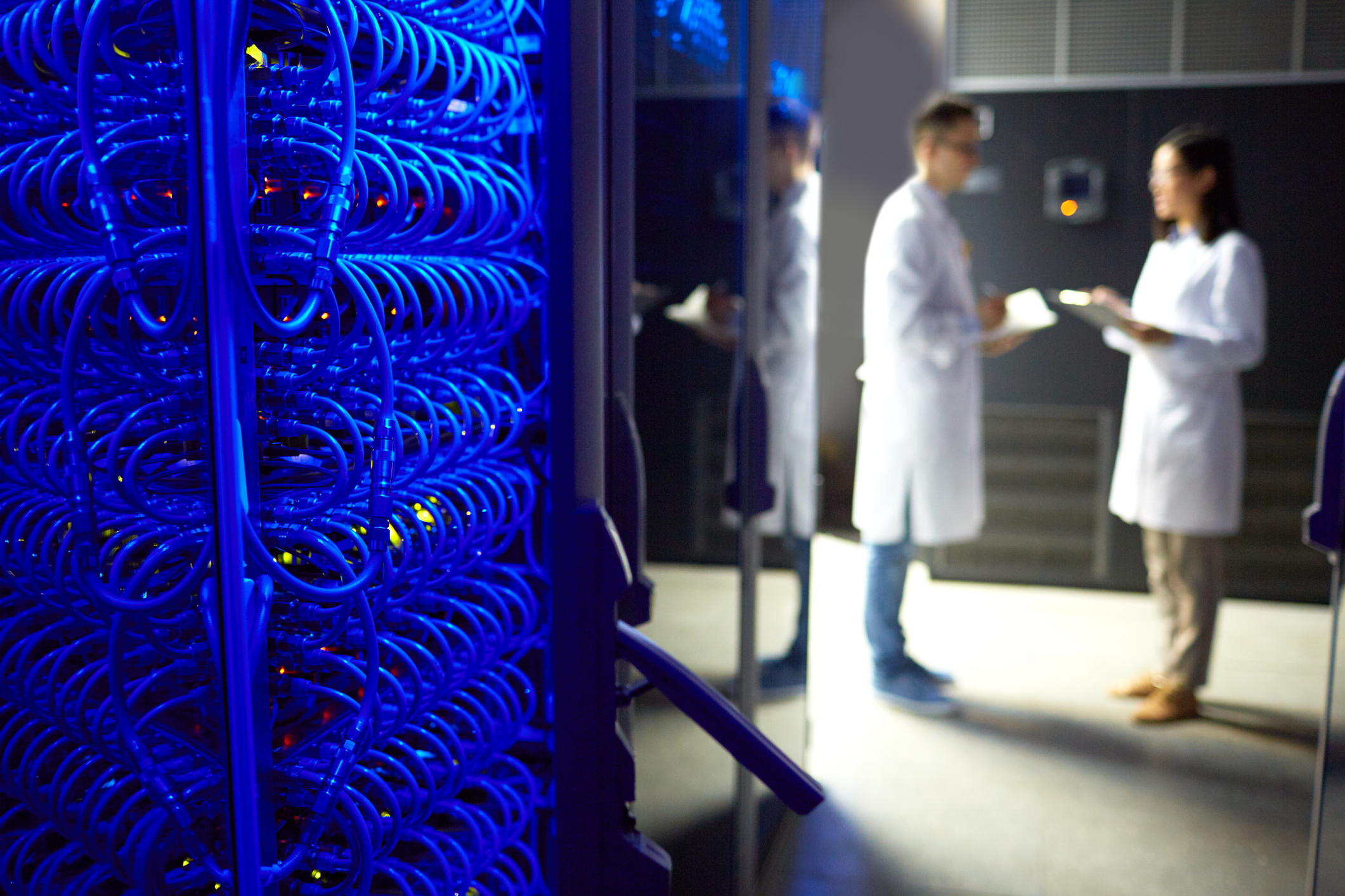 Two technicians stand near a supercomputer