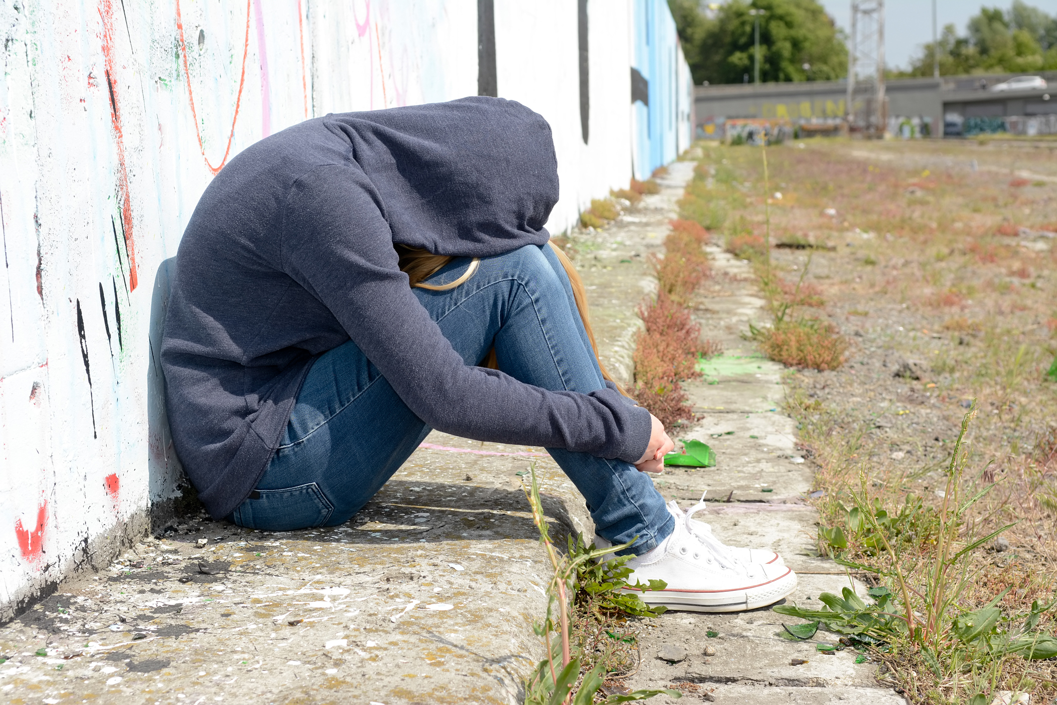 A young woman in a hoody sitting down with head on knees (Thinkstock/PA)