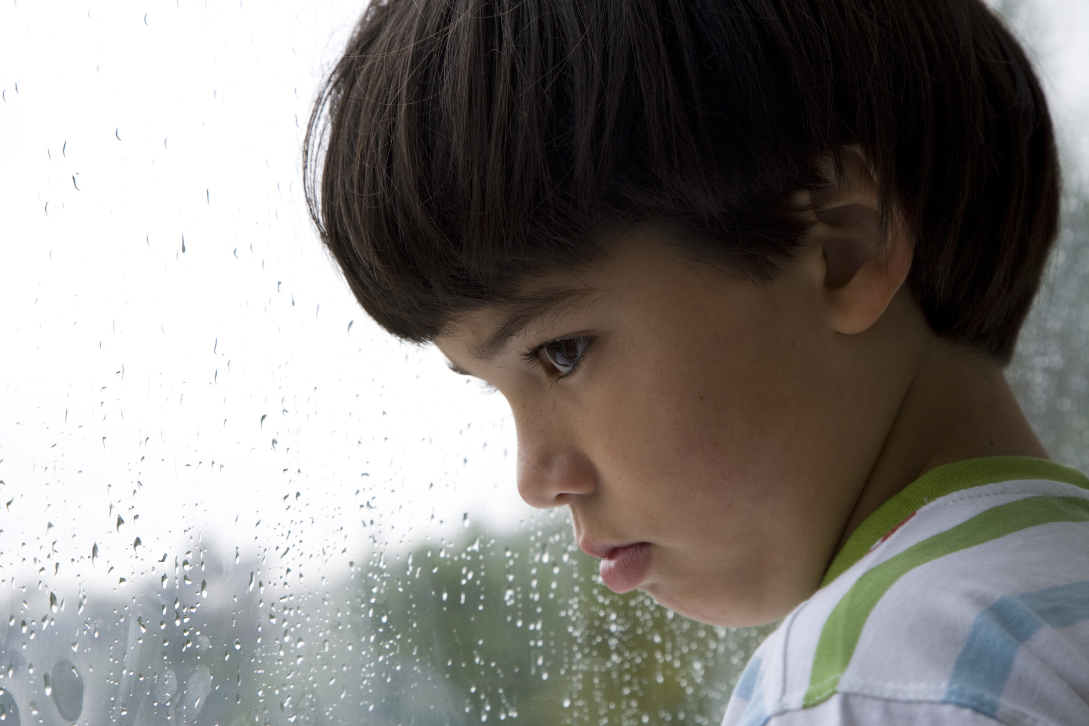 Close-up of a boy looking out a window on a rainy day (Thinkstock/PA)