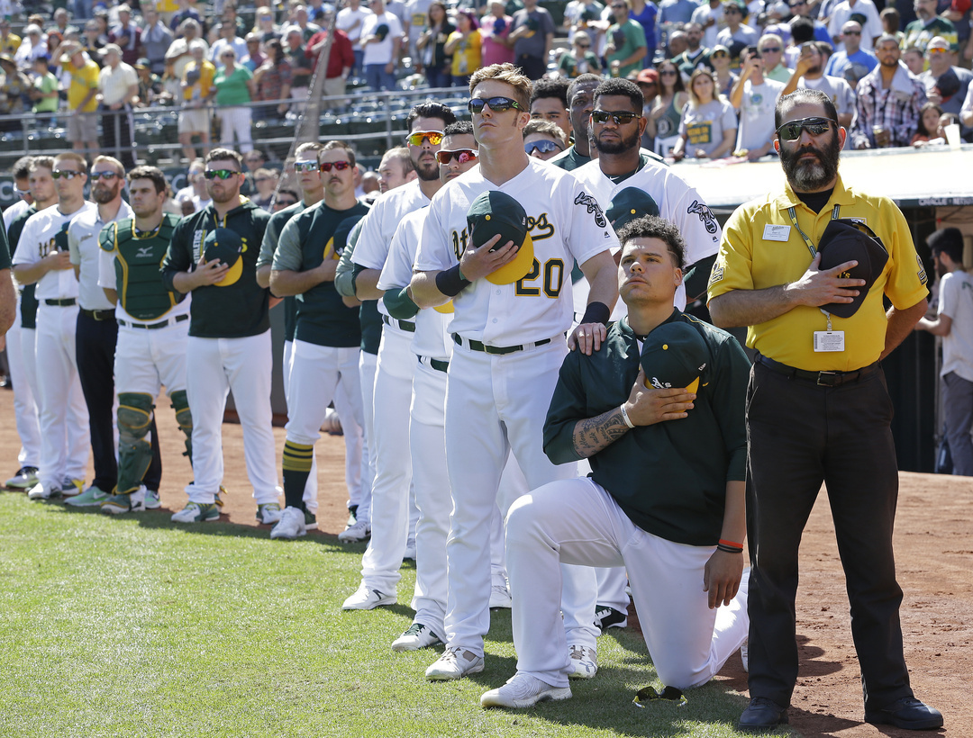Oakland Athletics' Mark Canha (20) places his hand on the shoulder of Bruce Maxwell