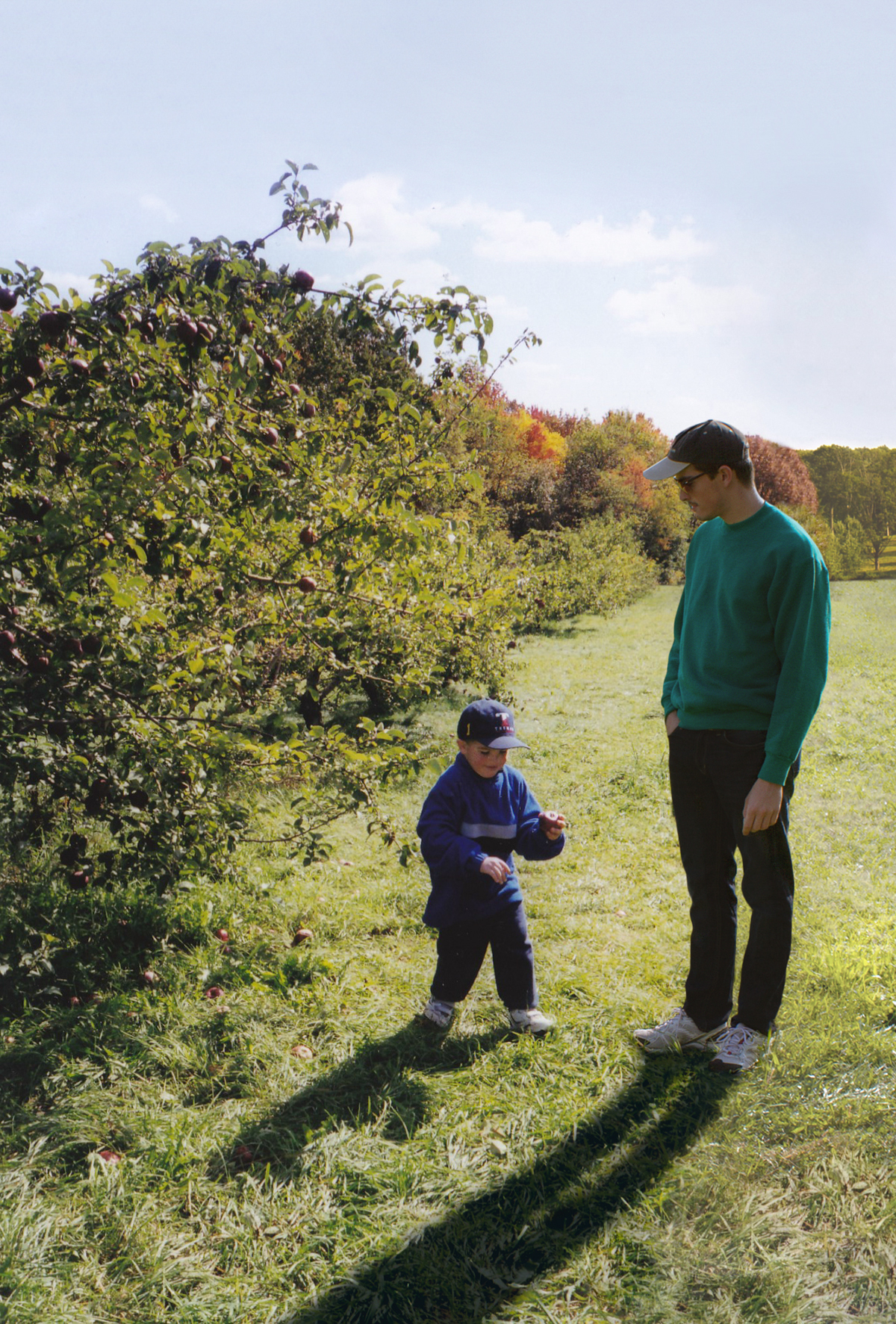 Conor and his younger self in an orchard