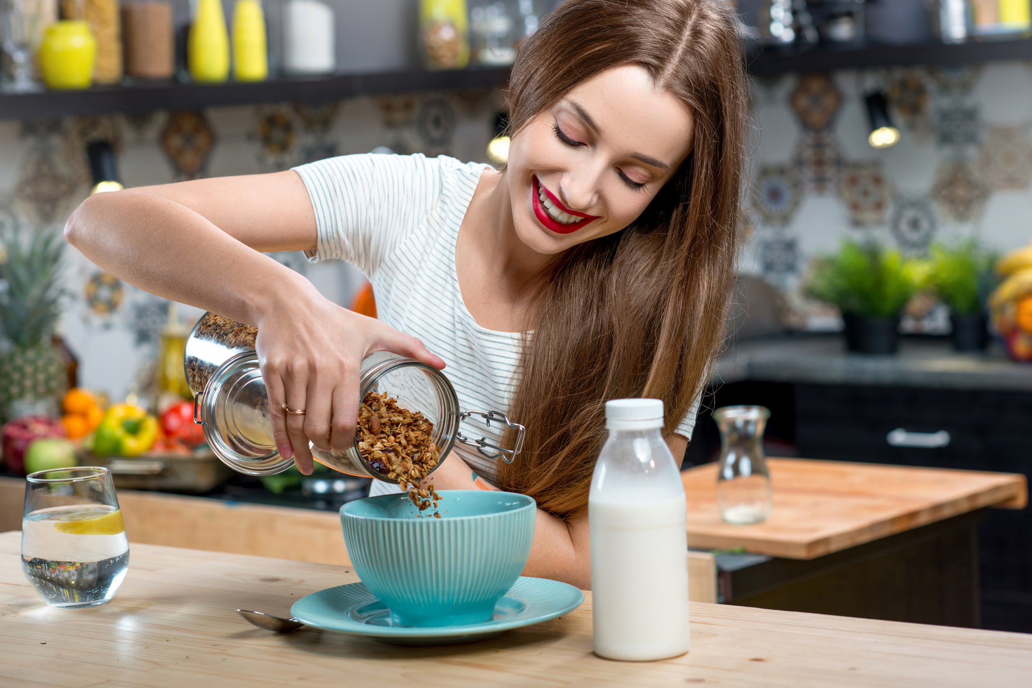 Young woman making breakfast with granola and milk in the modern kitchen at home (Thinkstock/PA)