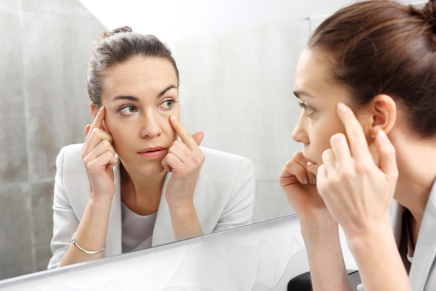Woman looks in the mirror noticing the first wrinkles