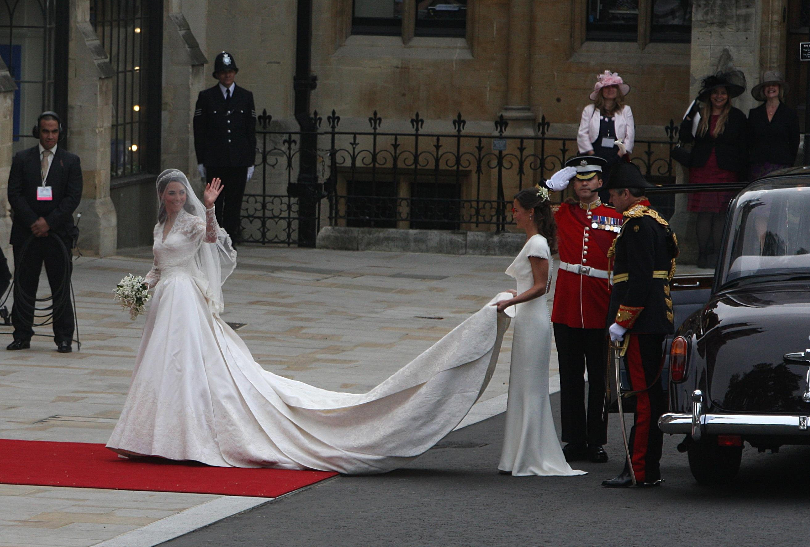 Kate Middleton waves as she arrives at Westminster Abbey where she is helped with her dress by her sister Pippa ahead of her wedding with Prince William.