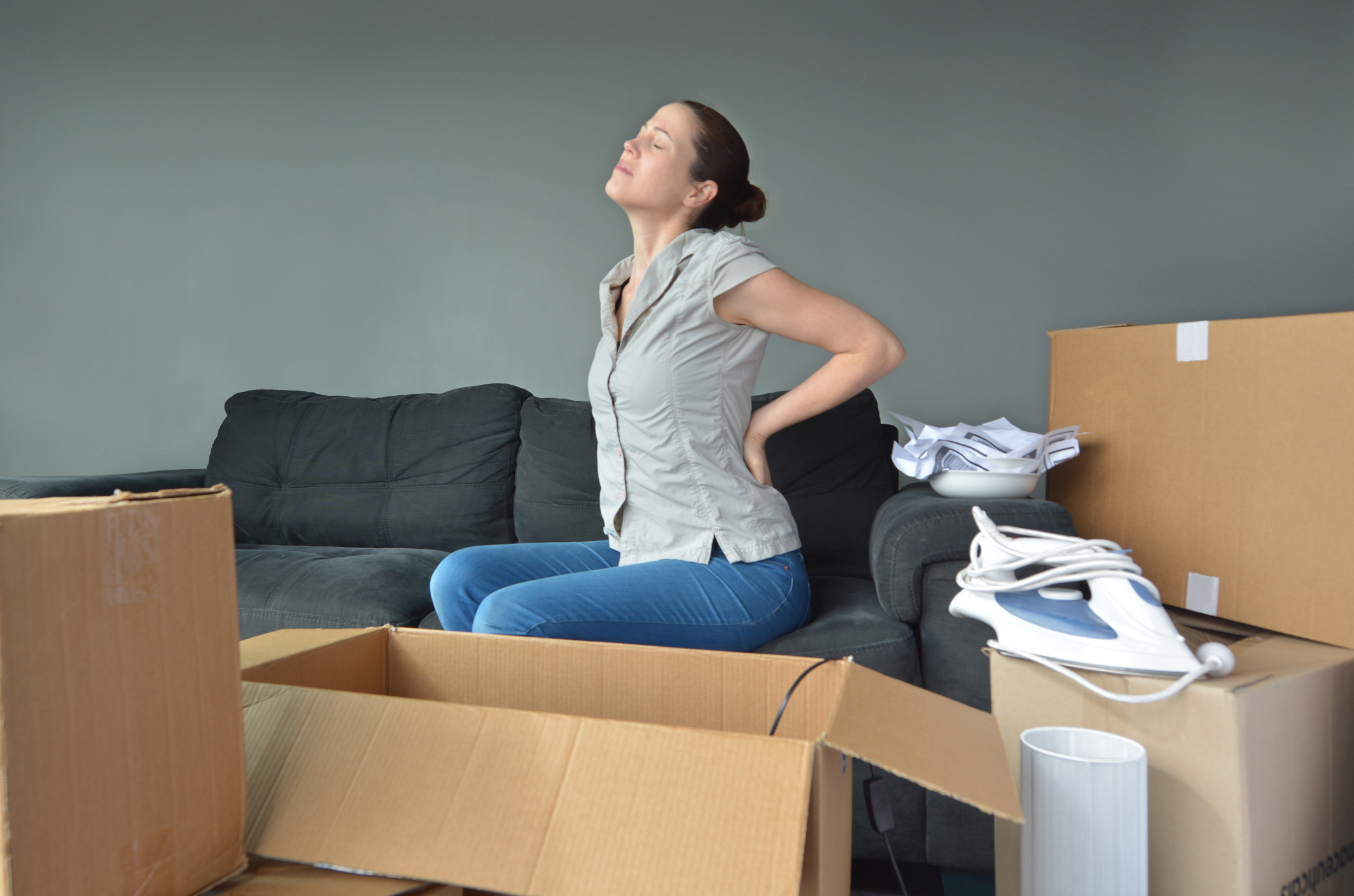 Woman holding her back in pain while surrounded by boxes (Thinkstock/PA)
