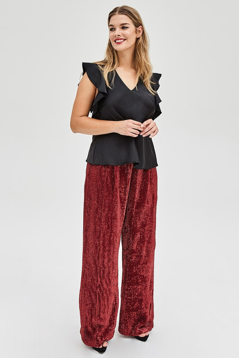 model wearing Elvi Black Satin Ruffle Top and Red Sequin Trousers