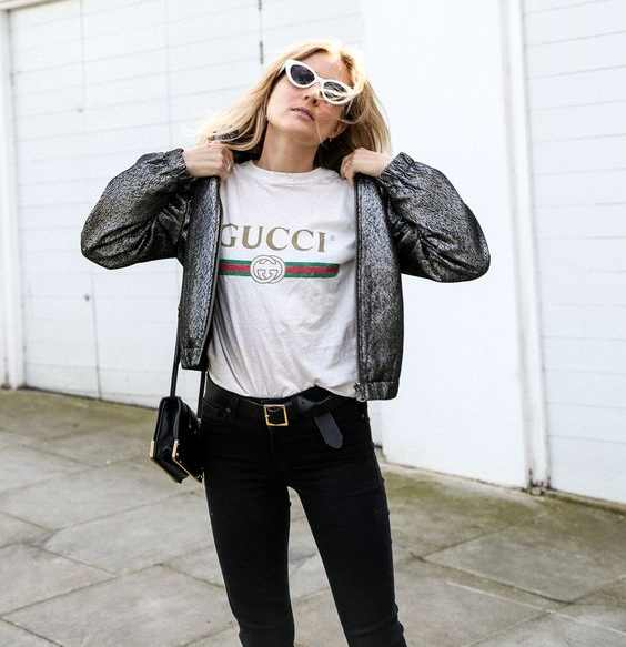 woman wearing a Gucci logo T-shirt, black jeans and a grey jacket