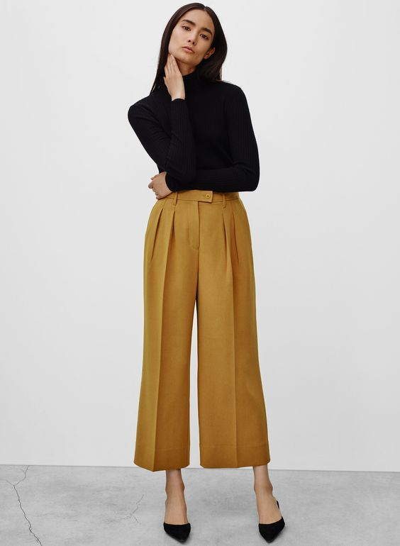 woman wearing camel coloured wide leg cropped trousers and a black polo neck