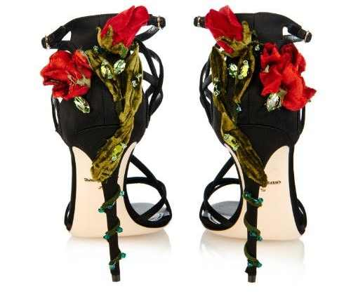 a pair of black high heeled shoes with rose embellishment