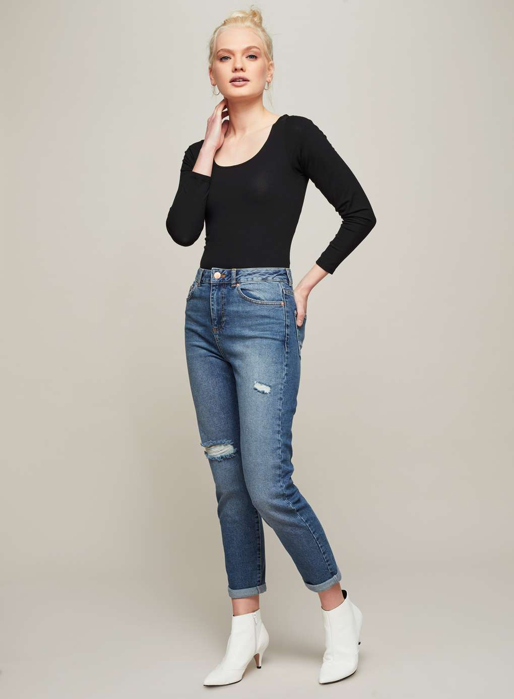 model wears black top, jeans and white boots from miss selfridge