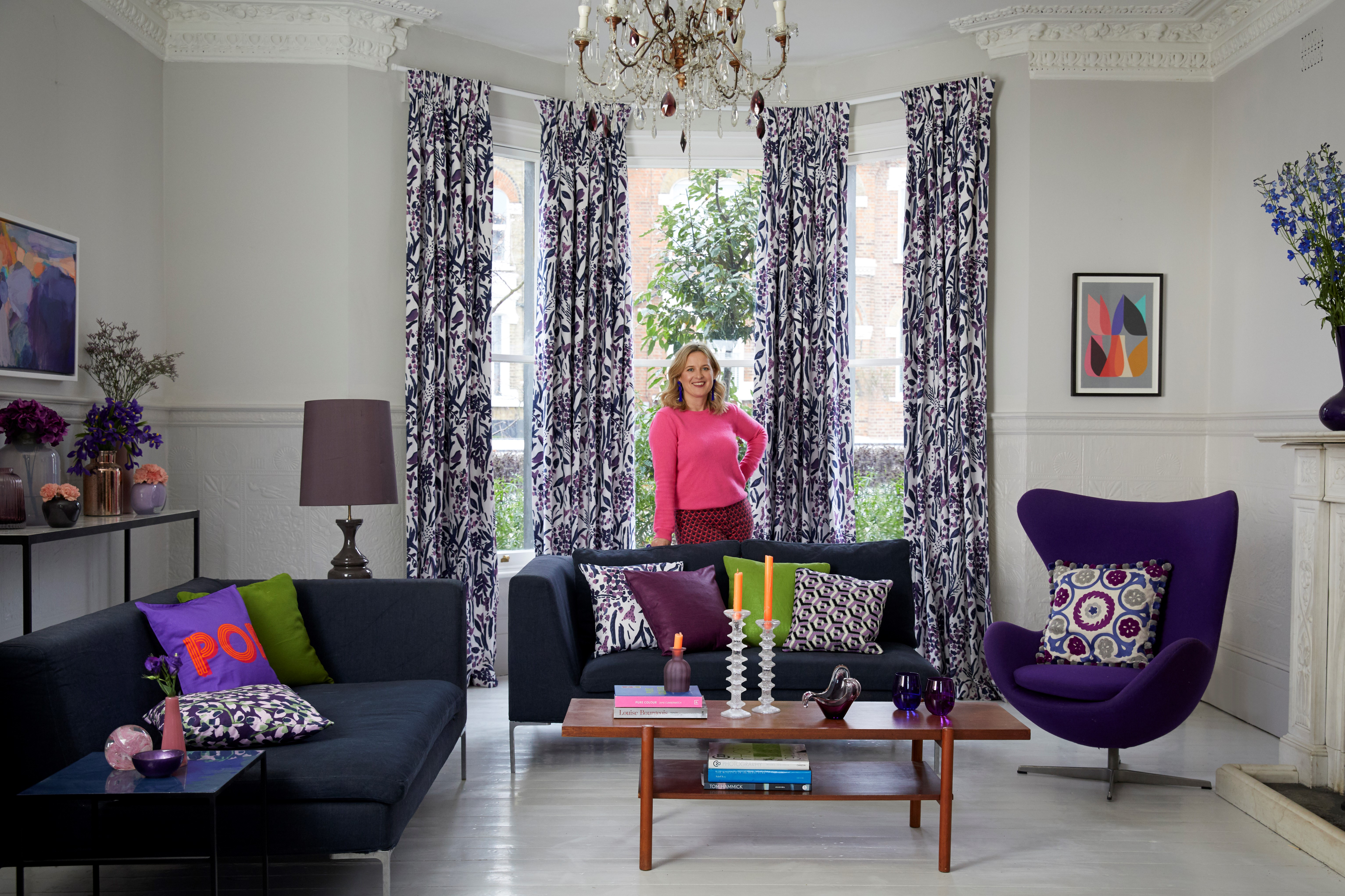 Sophie Robinson makes purple rock in her living room, with window's dressed with Sorana Violet fabric curtains, from £180, Hillarys, complemented by purple upholstered furniture, touches of lilac, coral, rose and indigo, plus pops of neon pink and acid green (Hillarys/PA)