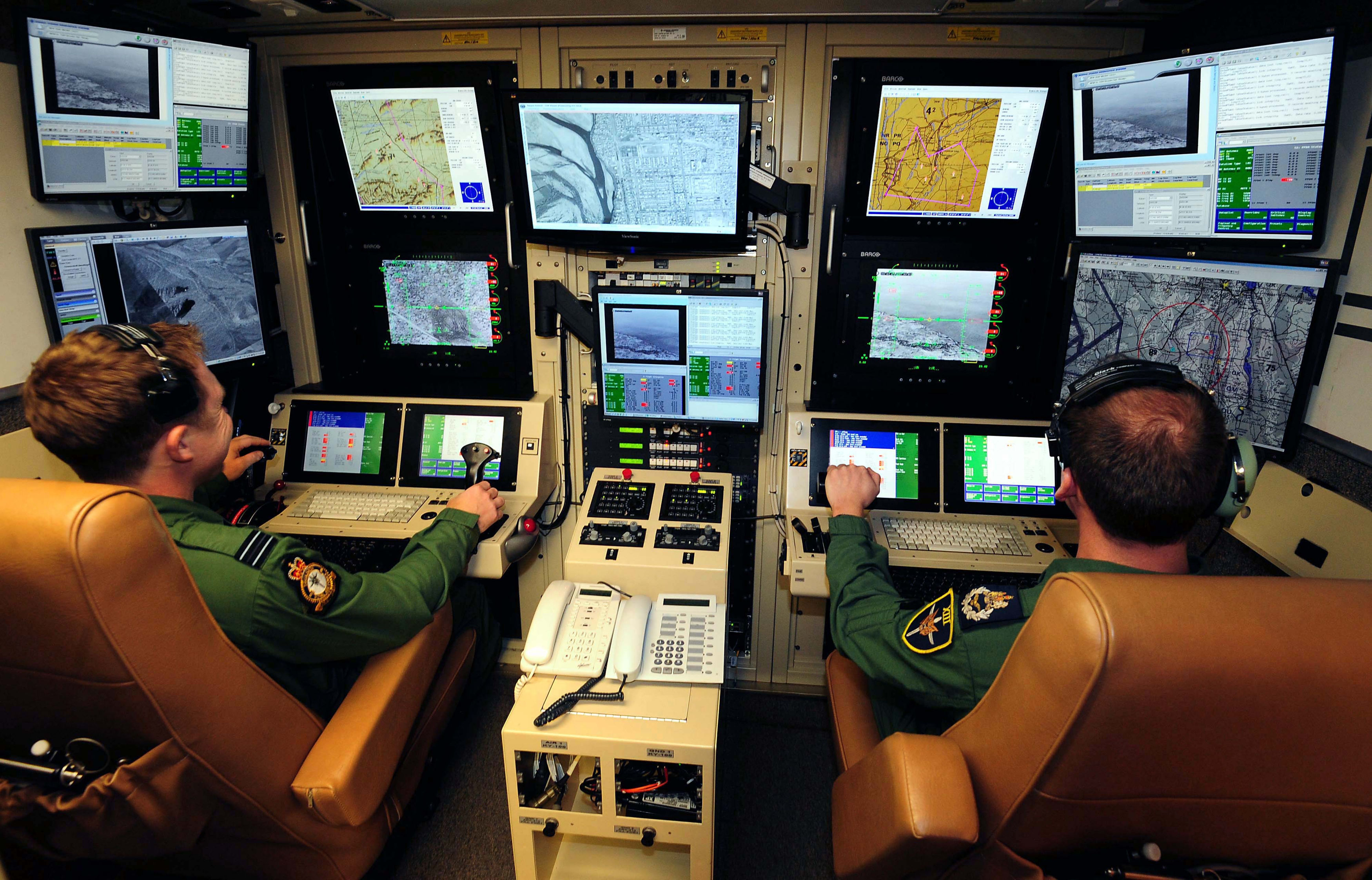 Operators sitting in the ground control operating station for a remotely piloted air system in the RAF
