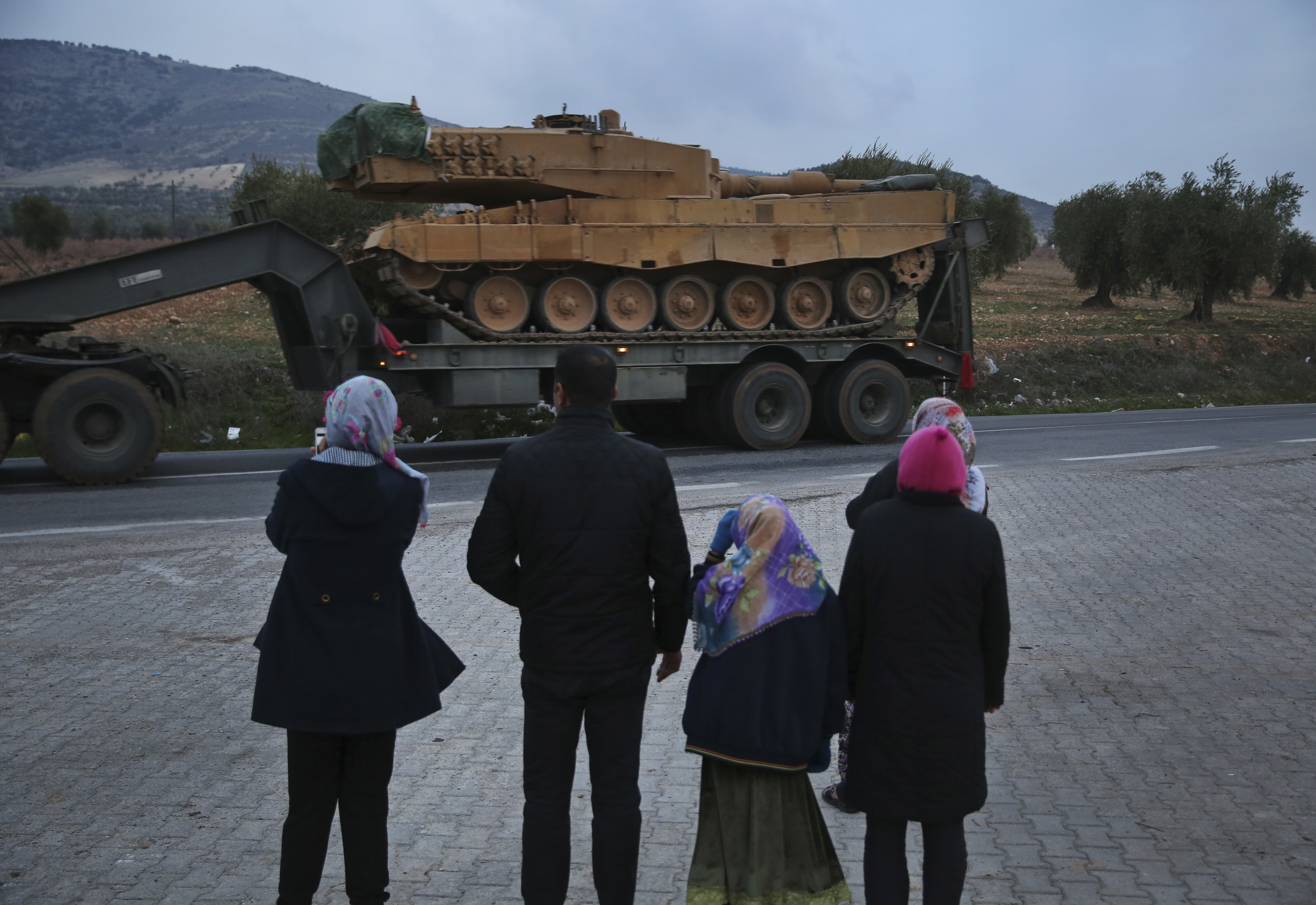Residents watch as a truck, part of a convoy, transporting a Turkish army tank is driven in the outskirts of the town of Kilis, Turkey, near the border with Syria (Lefteris Pitarakis/AP)