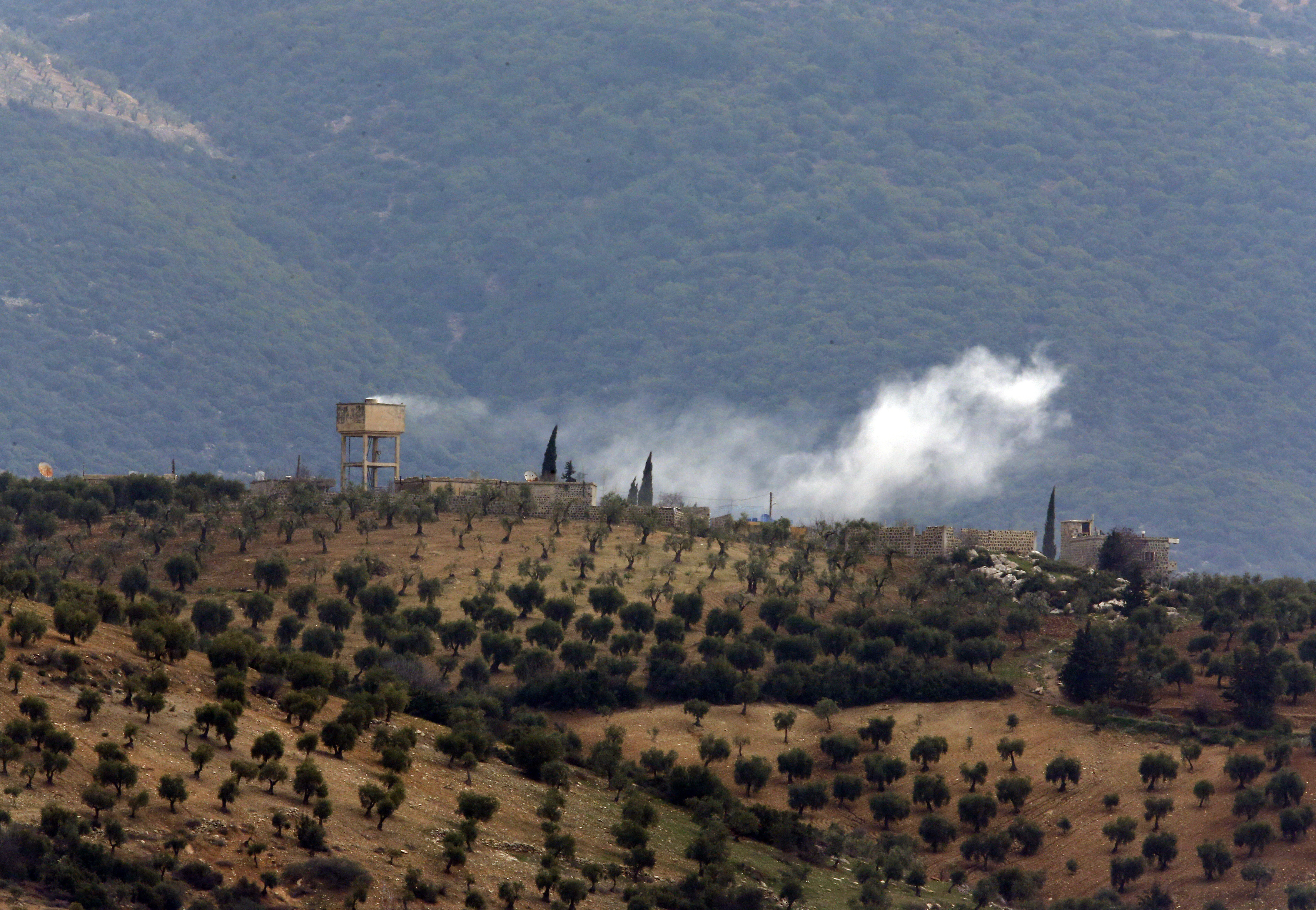Smoke billows from a position inside Syria, after a Turkish army artillery fired (Lefteris Pitarakis/AP)