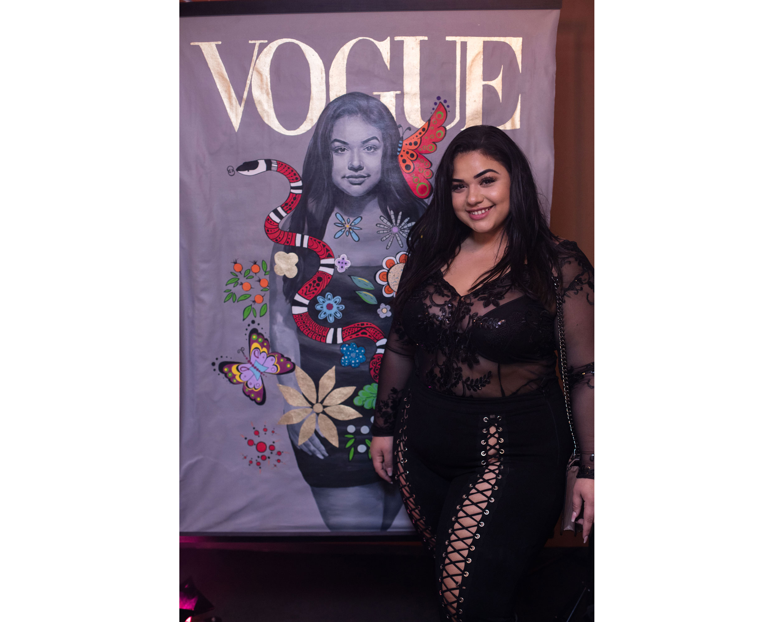 Diana Sirokai poses next to a painting depicting her on the cover of Vogue