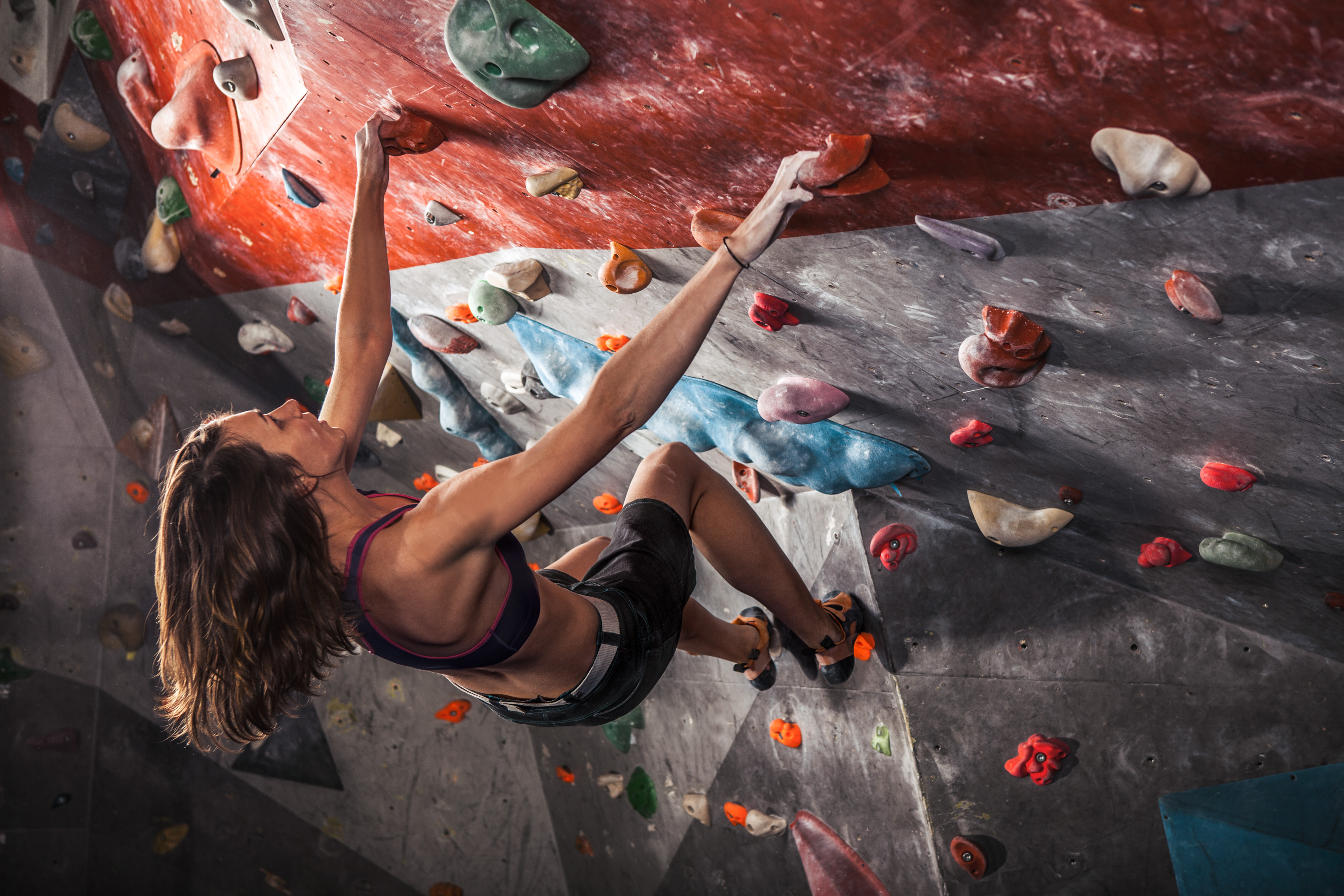 Young woman training on practice climbing wall indoo