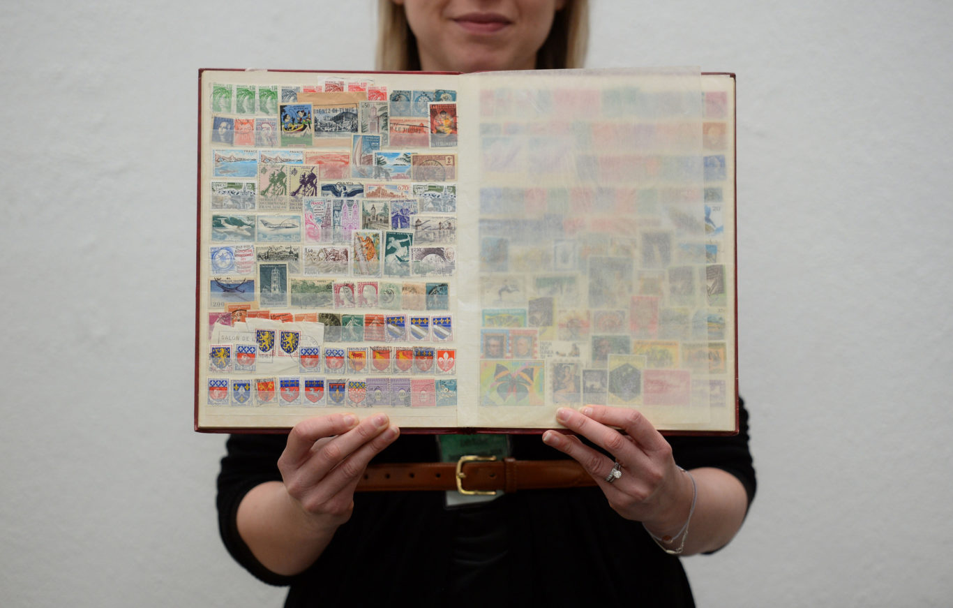 A visitor holds a stamp album from the collection (Kirsty O'Connor/PA)