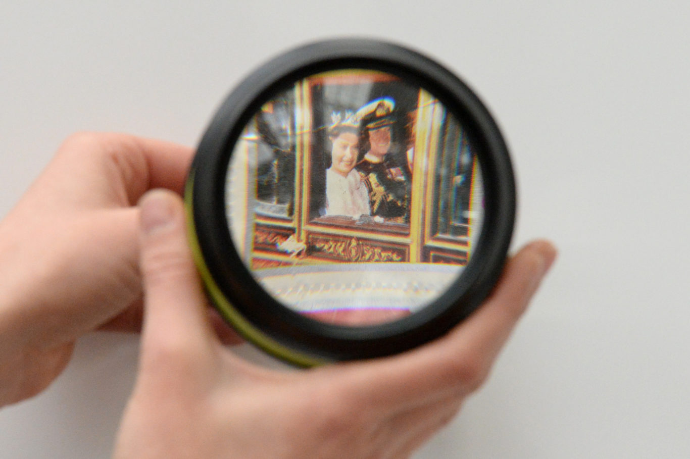 A visitor looks at a Silver Jubilee stamp through a magnifying glass (Kirsty O'Connor/PA)