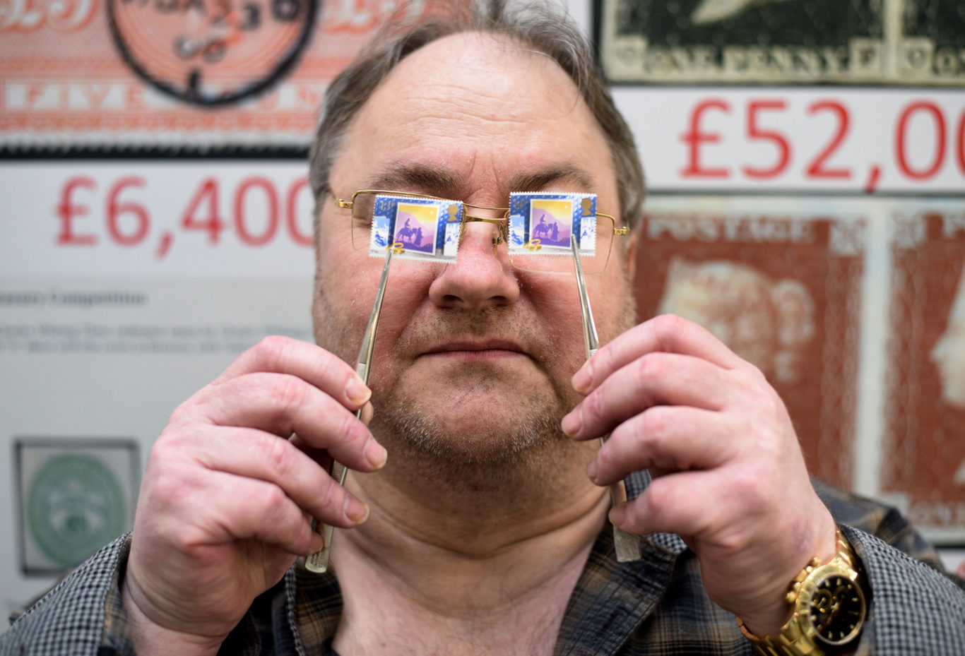 Stamp dealer Mark Bloxham holds up an SG1414a 1988 13p Christmas stamp (left) worth £8,000, next to a 14p version worth 14p (Kirsty O'Connor/PA)