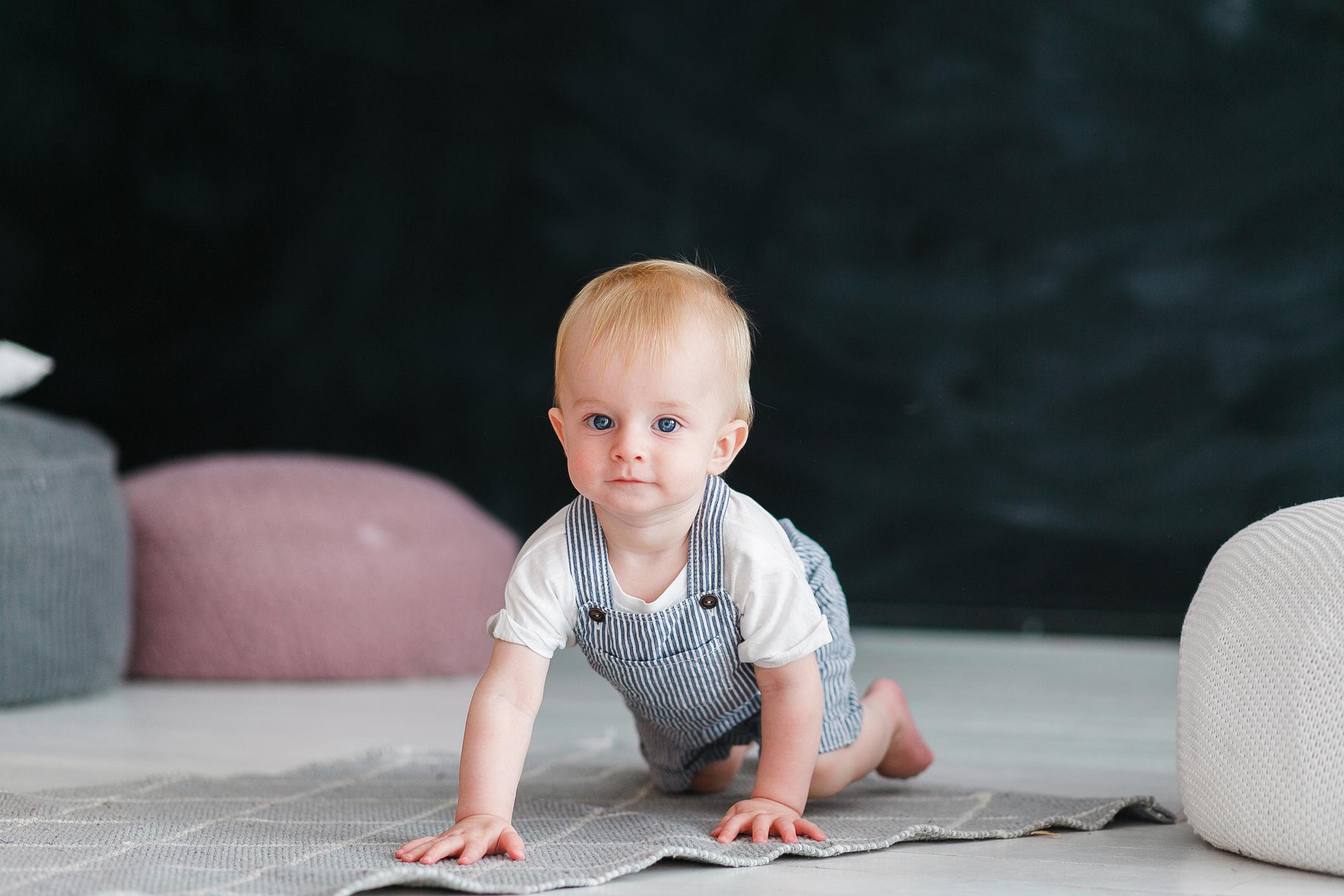Little baby crawls on floor in black background.